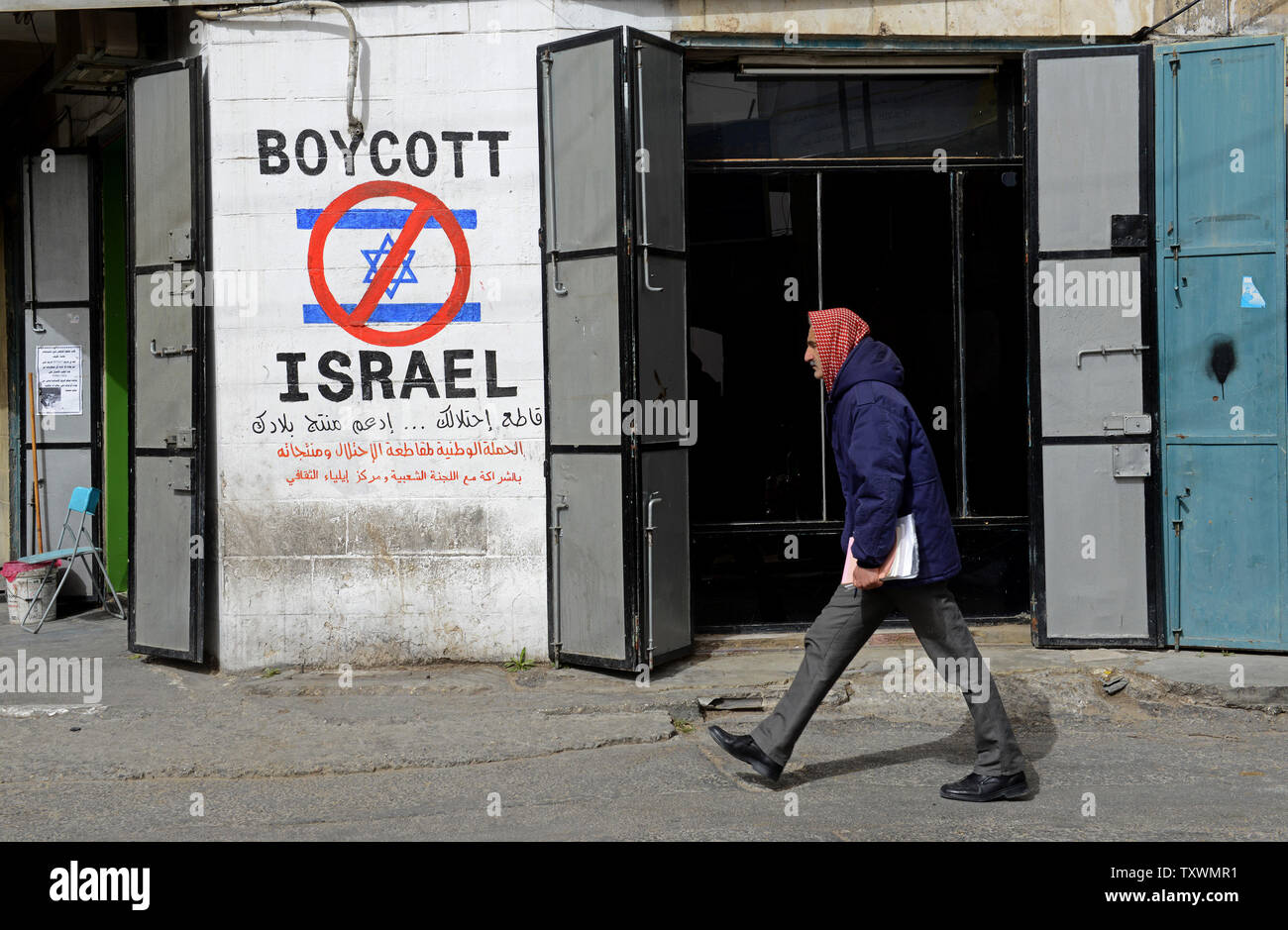 A Palestinian walks by graffiti reading 'Boycott Israel' at the entrance to the Beit Jibrin Refugee Camp in Bethlehem, West Bank, February 11, 2015. A high level national Palestinian committee announced it has instructed stores across the West Bank to ban products from six major Israeli companies, which are: Tnuva, the Strauss Group, Osem, Elite Prigate and Jafora-Tabori. The ban is meant to countermeasure Israel's decision to withhold Palestinian tax revenue it collects on behalf of the Palestinian Authority. West Bank grocers  must stop selling Israeli products within two weeks from today. P - Stock Image