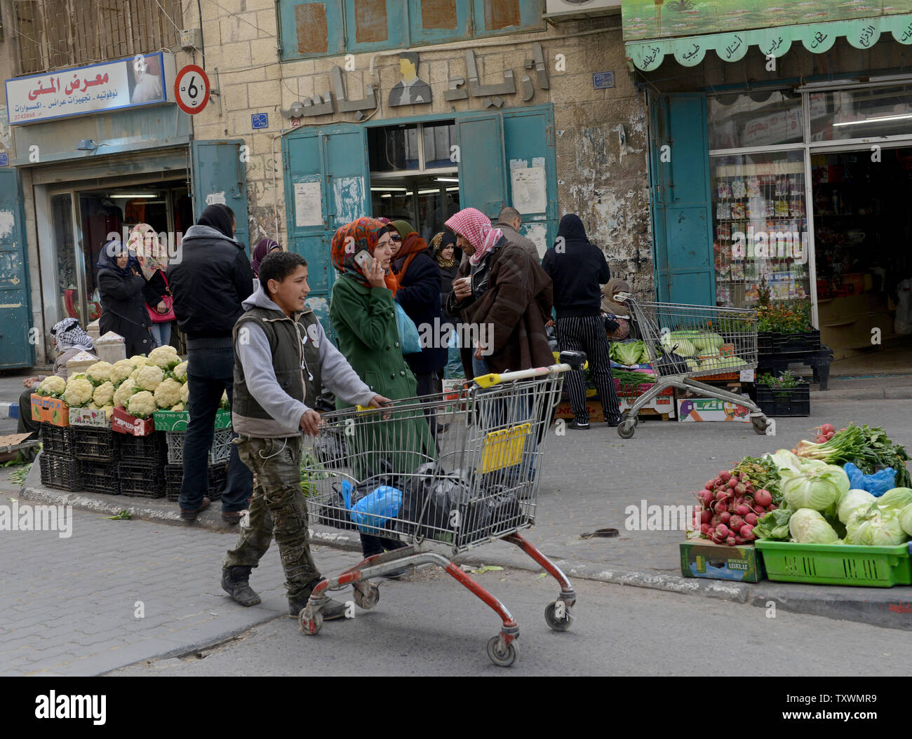 Palestinians shop in the Old City in Bethlehem, West Bank, February 11, 2015. A high level national Palestinian committee announced it has instructed stores across the West Bank to ban products from six major Israeli companies, which are: Tnuva, the Strauss Group, Osem, Elite Prigate and Jafora-Tabori. The ban is meant to countermeasure Israel's decision to withhold Palestinian tax revenue it collects on behalf of the Palestinian Authority. West Bank grocers  must stop selling Israeli products within two weeks from today. Photo by Debbie Hill/UPI - Stock Image