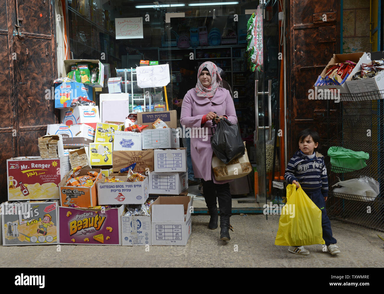 A Palestinian leaves a shop selling Israeli products in the Old City in Bethlehem, West Bank, February 11, 2015. A high level national Palestinian committee announced it has instructed stores across the West Bank to ban products from six major Israeli companies, which are: Tnuva, the Strauss Group, Osem, Elite Prigate and Jafora-Tabori. The ban is meant to countermeasure Israel's decision to withhold Palestinian tax revenue it collects on behalf of the Palestinian Authority. West Bank grocers  must stop selling Israeli products within two weeks from today. Photo by Debbie Hill/UPI - Stock Image