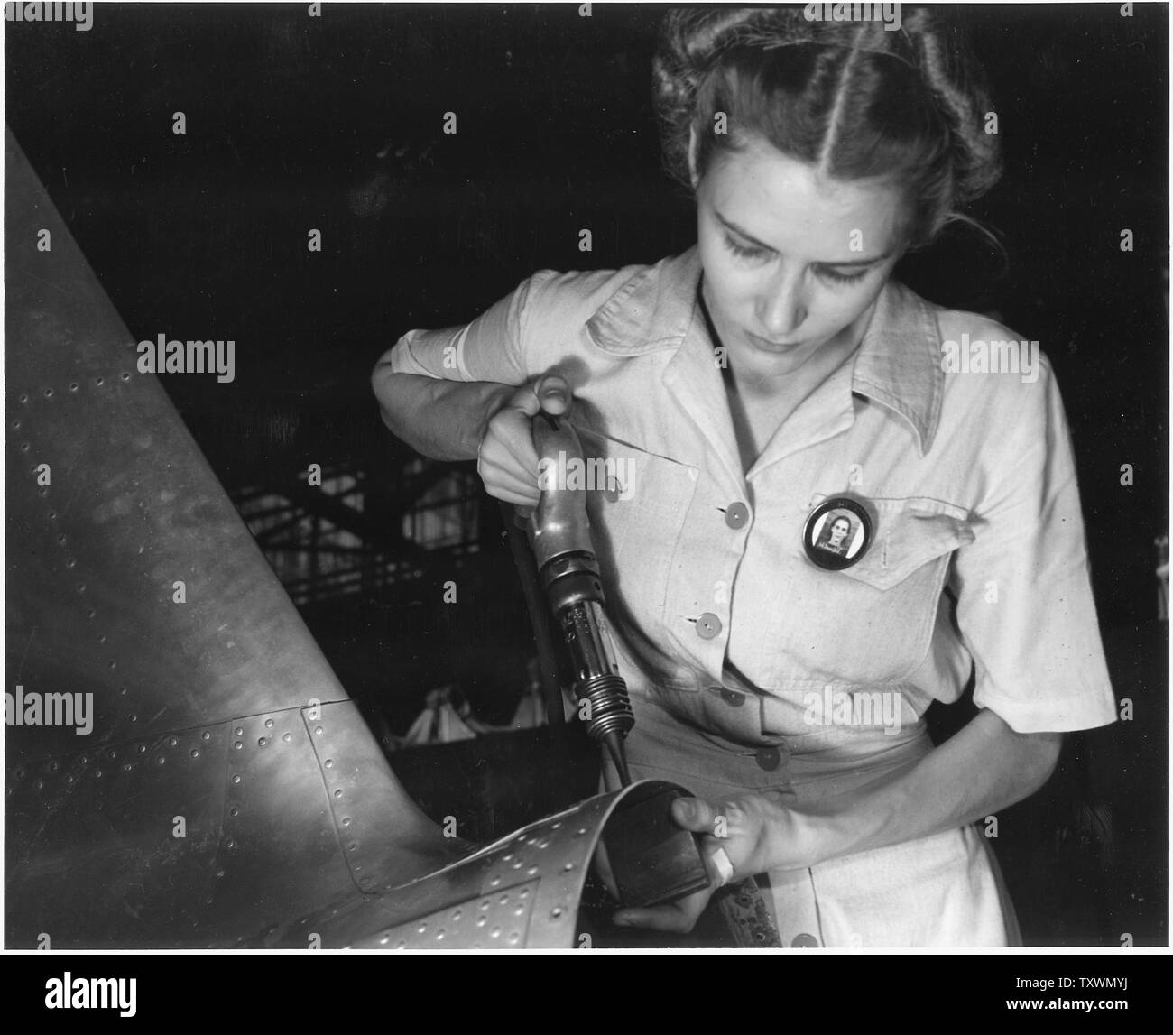 Answering the nation's need for womanpower, Mrs. Virginia Davis made arrangements for the care of her two children during the day and joined her husband at work in the Naval Air Base in Corpus Christi, Texas. - Stock Image