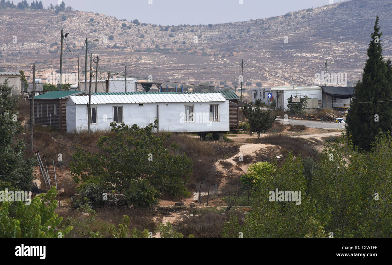 Houses stand in the unauthorized Jewish outpost Amona, east of the Palestinian city Ramallah, West Bank, August 15, 2016. The Israeli Supreme Court has ordered the government to tear down the outpost by the end of 2016, while the government is set to move the illegal West Bank outpost to adjacent Palestinian land 'abandoned' in 1967. Israel has received harsh criticism from America who views the plan to move the outpost to West Bank Palestinian land as deviating from Israeli Prime Minister Benjamin Netanyahu's commitment to U.S. President Barack Obama that Israel would not appropriate Palestin - Stock Image