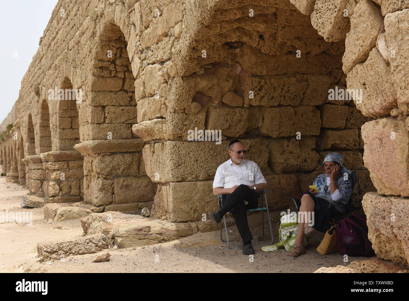 Israelis sit in the shade in the squeduct in Caesarea, Israel, April 26, 2017. The Edmond de Rothschild Foundations is investing approximately $275,000 to expose and restore Caesarea's hidden treasures.  Photo by Debbie Hill/UPI - Stock Image