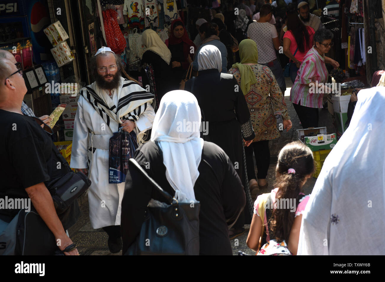 An Ultra-Orthodox Jew wears and white robe and prayer shawl while walking between Muslim women in the Old City of Jerusalem, on Rosh HaShanah, the Jewish New Year, and the Islamic New Year, September 21, 2017. Both religions follow the lunar calendar. Photo by Debbie Hill/UPI Stock Photo