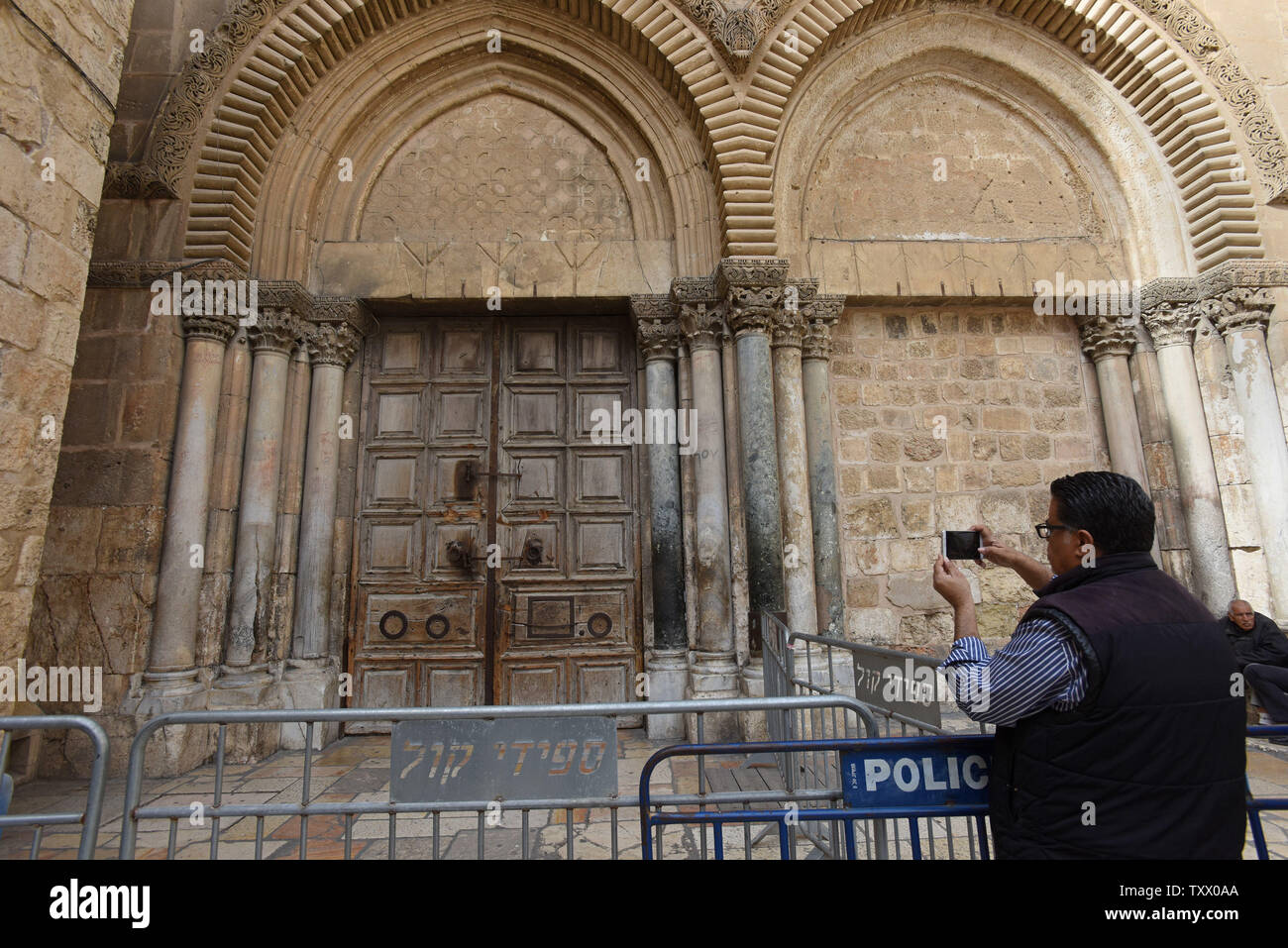 A tourist takes a photo of the locked doors of the Church of the