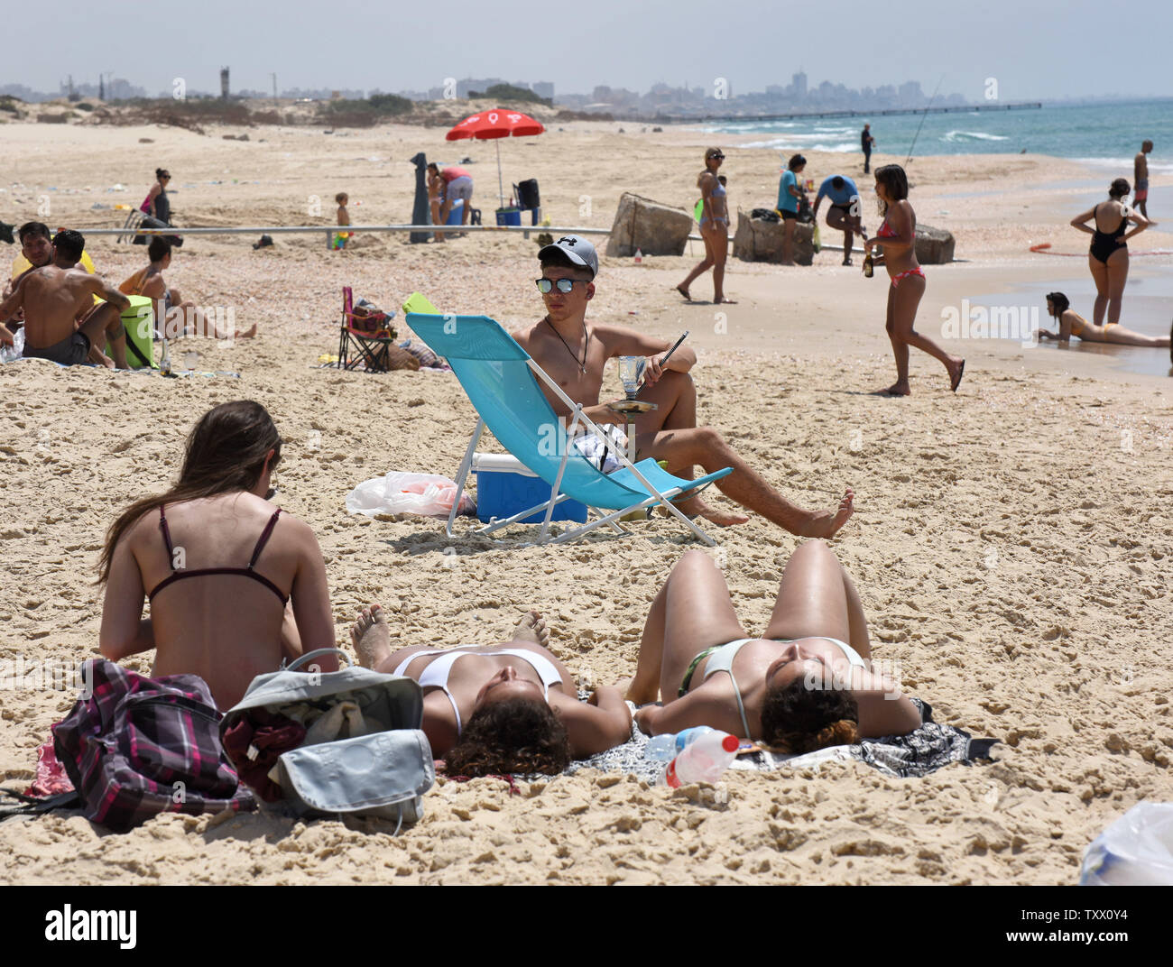 The Gaza skyline is seen in the distance behind Israelis enjoying temperatures reaching 105 degrees, at the Zikim Beach, Israel, near the Gaza Strip, May 18, 2018.  More than a hundred Palestinians have been killed by the Israeli army in protests along the Israel-Gaza border in recent weeks.   Photo by Debbie Hill/UPI - Stock Image
