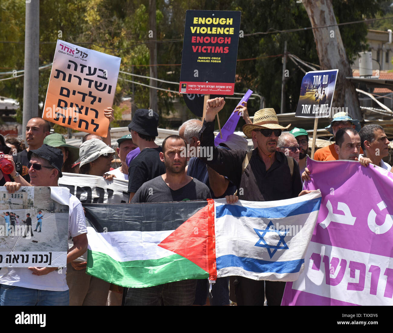 Israeli protesters hold the Israeli and Palestinian national flags and signs calling on the government to stop the bloodshed of Palestinians on the Gaza border at a demonstration at  Yad Mordechai, Israel, near the Gaza Strip, May 18, 2018.  More than a hundred Palestinians have been killed by the Israeli army in protests along the Israel-Gaza border in recent weeks.   Photo by Debbie Hill/UPI - Stock Image