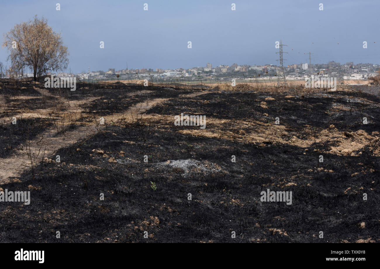 Houses in the Gaza Strip are seen behind fields in Kibbutz Nahal Oz, on the Israeli- Gaza border, that were burned by fires started by kites sent by Palestinian protesters in Gaza, June 5, 2018. Over 600 kites have been flown into Israel from the Gaza Strip, destroying 9000 square meters of crops and forests.    Photo by Debbie Hill/UPI - Stock Image