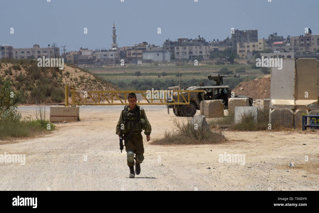 Houses in the Gaza Strip are seen behind an Israeli soldier on the Israeli- Gaza border, near Kibbutz Nahal Oz, June 5, 2018. Over 600 kites have been flown into Israel from the Gaza Strip, destroying 9000 square meters of crops and forests.    Photo by Debbie Hill/UPI - Stock Image