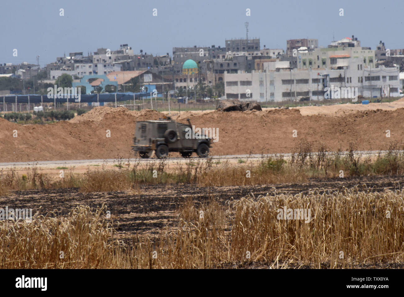Houses in the Gaza Strip are seen behind an Israeli army jeep  on the Israeli- Gaza border, near Kibbutz Nahal Oz, June 5, 2018. Over 600 kites have been flown into Israel from the Gaza Strip, destroying 9000 square meters of crops and forests.    Photo by Debbie Hill/UPI - Stock Image