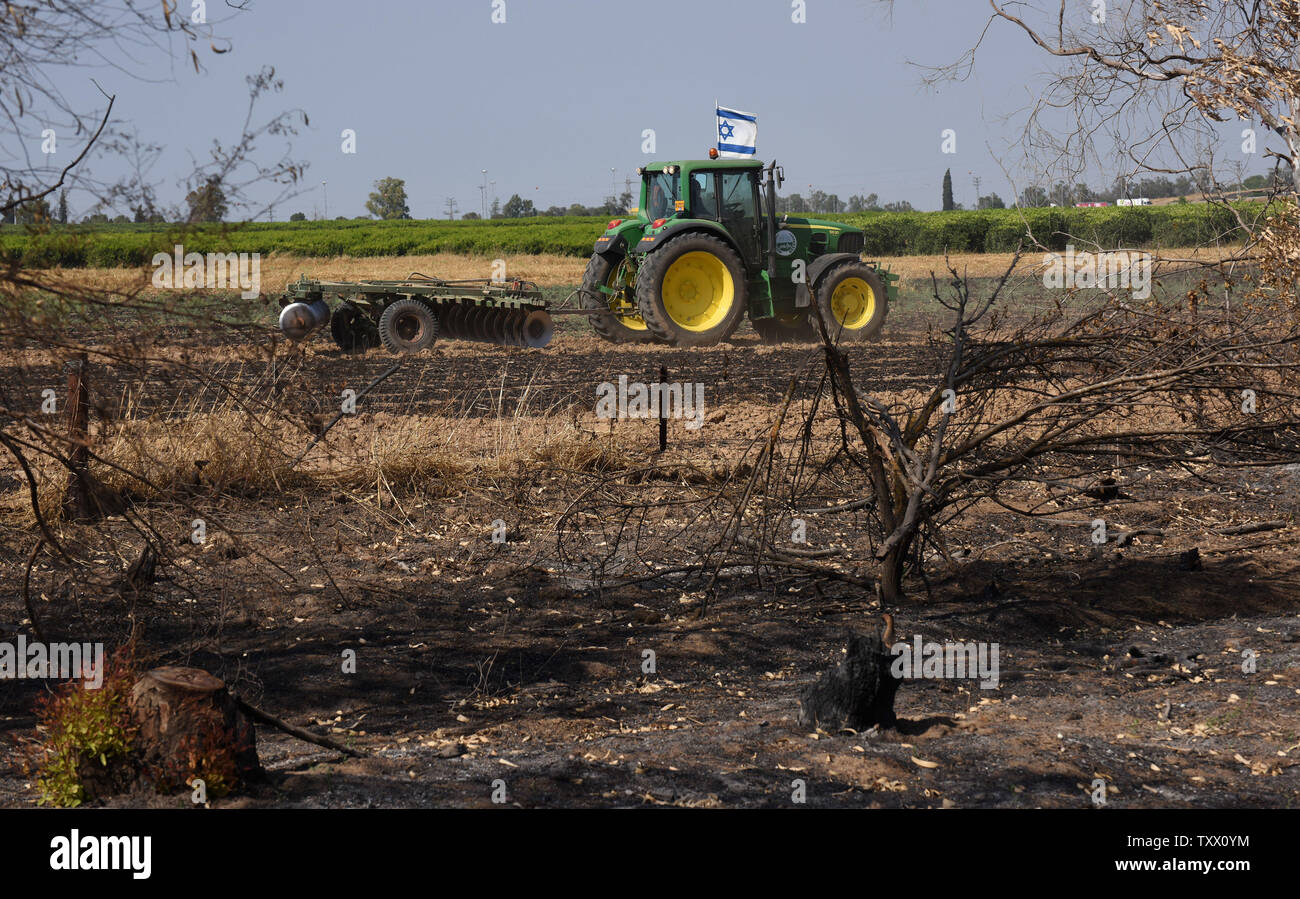 A tractor with an Israeli flag works in a field of Kibbutz Kfar Azza, near the border of the Gaza Strip, that was ignited by kites sent by Palestinian protesters in Gaza, June 5, 2018. Over 600 kites have been flown into Israel from the Gaza Strip, destroying 9000 square meters of crops and forests.    Photo by Debbie Hill/UPI - Stock Image