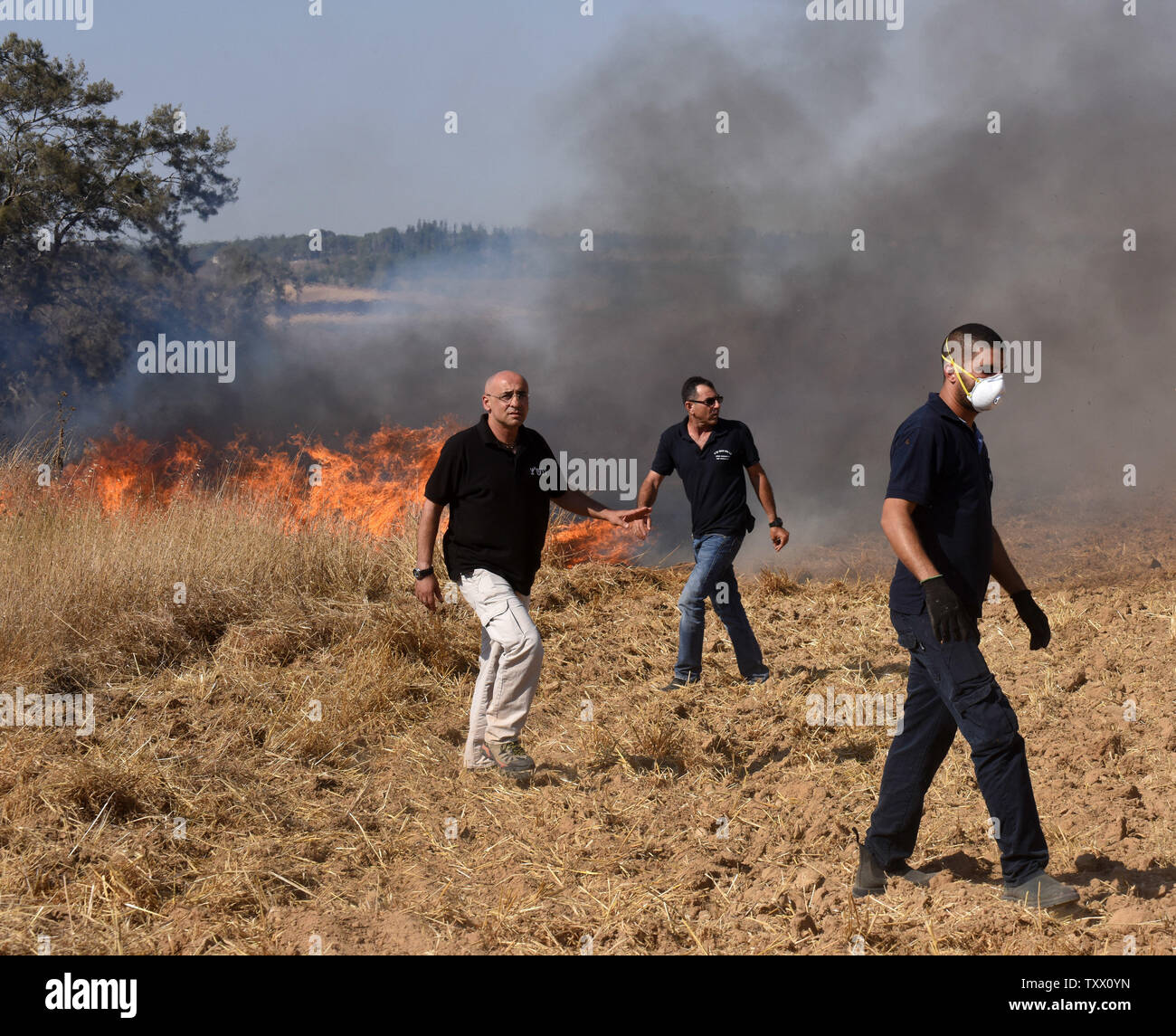 Israelis rush to a fire near Kibbutz Kfar Azza, along the border of the Gaza Strip, that was ignited by kites sent by Palestinian protesters in Gaza, June 5, 2018. Over 600 kites have been flown into Israel from the Gaza Strip, destroying 9000 square meters of crops and forests.    Photo by Debbie Hill/UPI - Stock Image