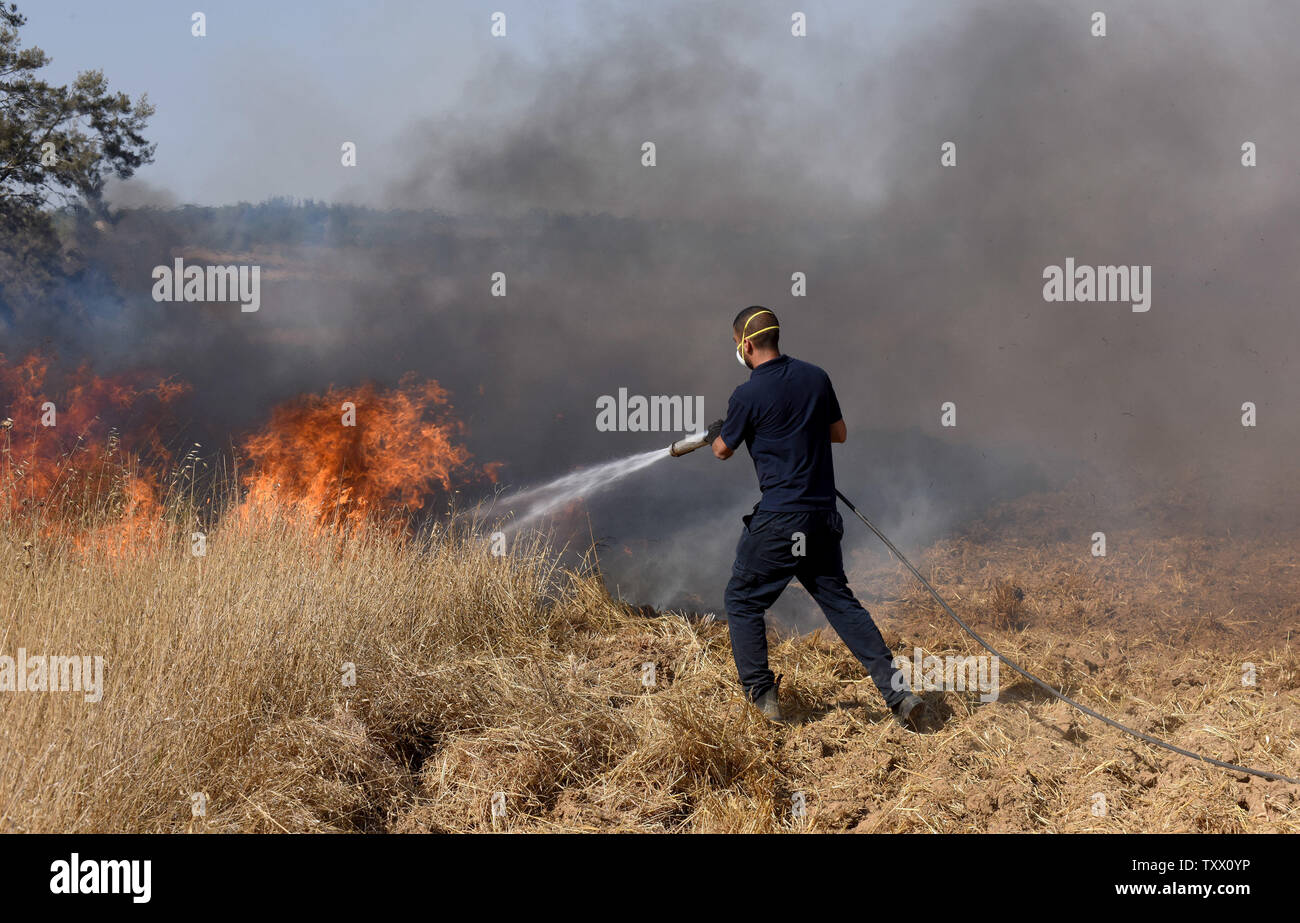 An Israeli firefighter attempts to extinguish a fire near Kibbutz Kfar Azza, along the border of the Gaza Strip, that was ignited by kites sent by Palestinian protesters in Gaza, June 5, 2018. Over 600 kites have been flown into Israel from the Gaza Strip, destroying 9000 square meters of crops and forests.    Photo by Debbie Hill/UPI - Stock Image