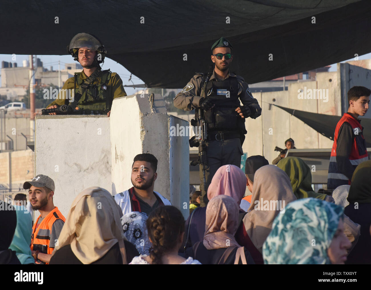 Israeli security forces guard Palestinians waiting to cross the Qalandiya checkpoint, West Bank, from Ramallah to Jerusalem, to pray at the Al-Aqsa Mosque on the last Friday of the Muslim holy month of Ramadan, June 8, 2018.  Photo by Debbie Hill/UPI - Stock Image