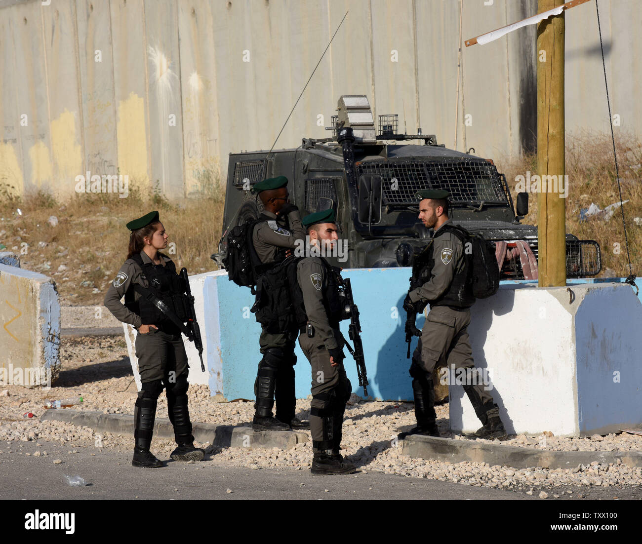 Israeli security forces guard Palestinians, not seen, waiting to cross the Qalandiya checkpoint, West Bank, from Ramallah to Jerusalem, to pray at the Al-Aqsa Mosque on the last Friday of the Muslim holy month of Ramadan, June 8, 2018.  Photo by Debbie Hill/UPI - Stock Image