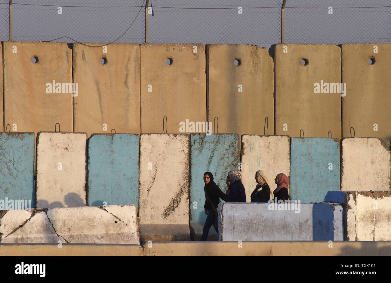 Palestinians walk past concrete barriers to cross the Qalandiya checkpoint, West Bank, to pray at the Al-Aqsa Mosque in Jerusalem, on the last Friday of the Muslim holy month of Ramadan, June 8, 2018.  Photo by Debbie Hill/UPI - Stock Image