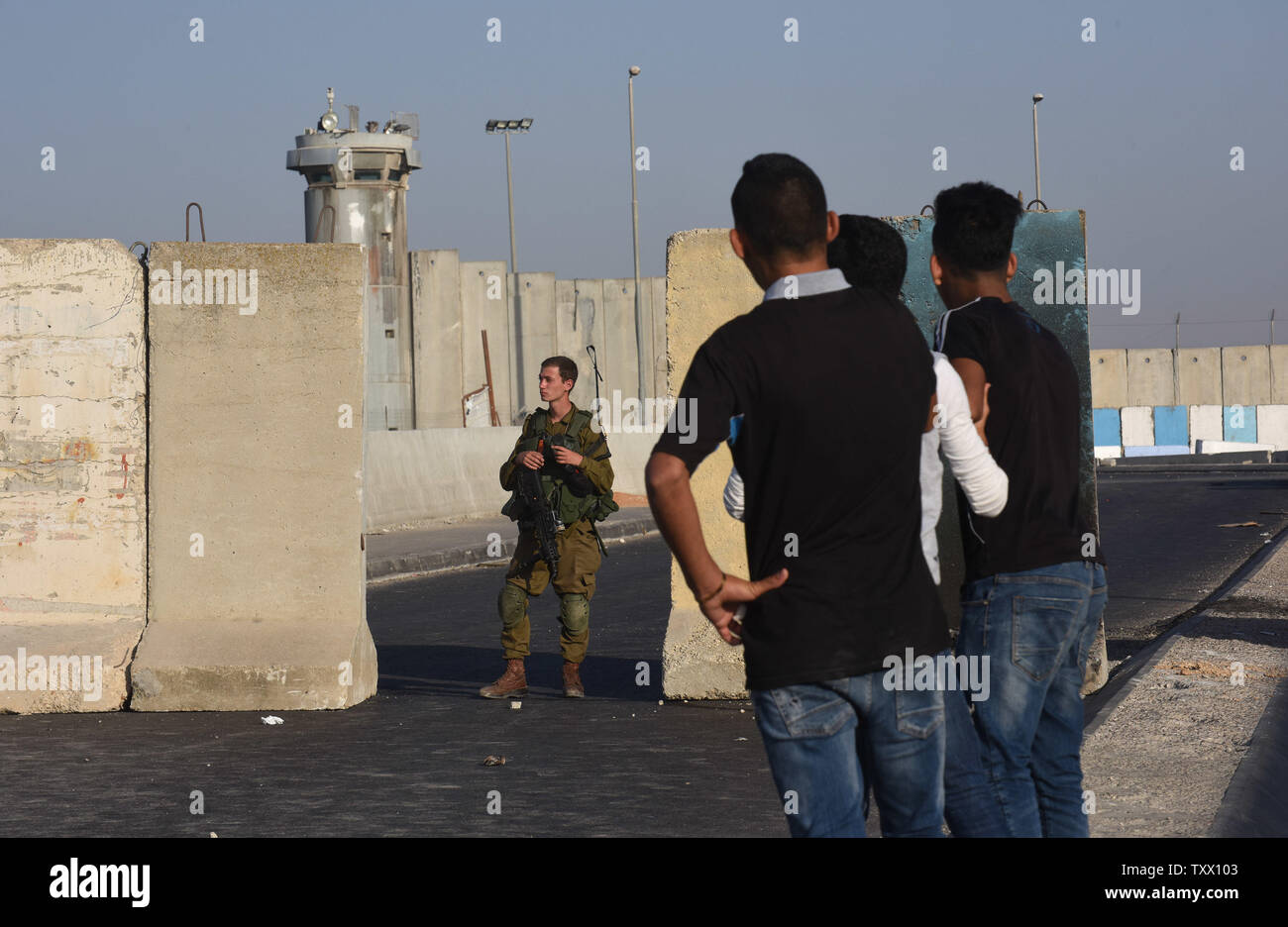 Palestinian youth look at an Israeli soldier at the Qalandiya checkpoint, West Bank, on the last Friday of the Muslim holy month of Ramadan, June 8, 2018.  Photo by Debbie Hill/UPI - Stock Image