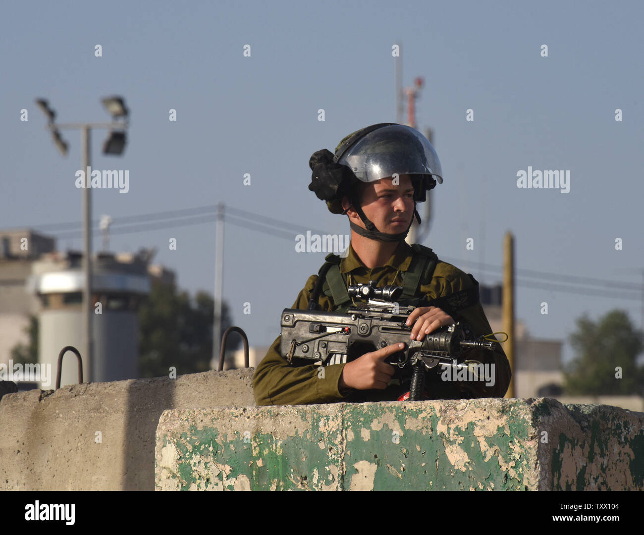An Israeli soldier guards Palestinians, not seen, waiting to cross the Qalandiya checkpoint, West Bank, from Ramallah to Jerusalem, to pray at the Al-Aqsa Mosque on the last Friday of the Muslim holy month of Ramadan, June 8, 2018.  Photo by Debbie Hill/UPI - Stock Image