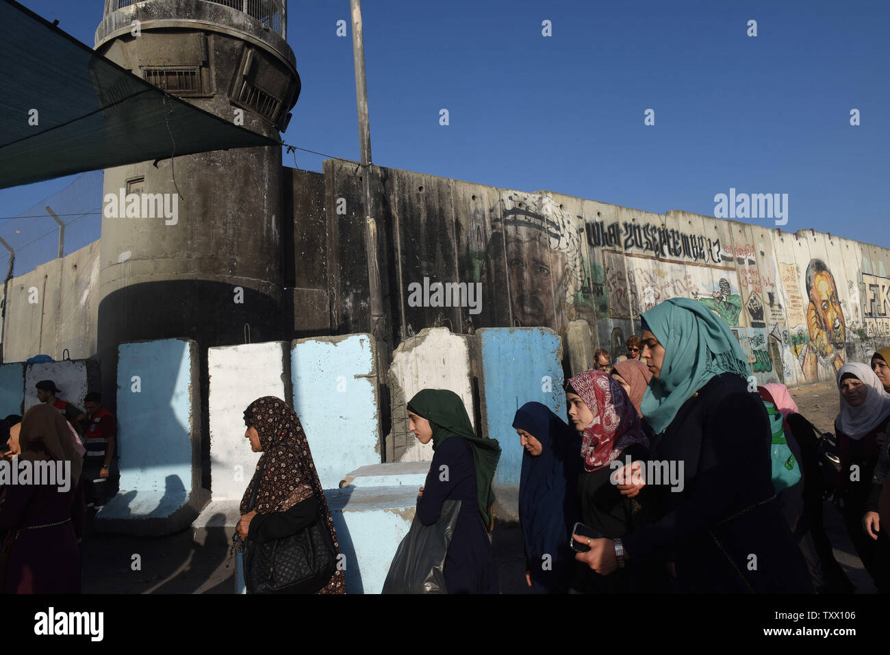 Palestinians wait in line to cross the Qalandiya checkpoint, West Bank, from Ramallah to Jerusalem, to pray at the Al-Aqsa Mosque on the last Friday of the Muslim holy month of Ramadan, June 8, 2018.  Photo by Debbie Hill/UPI - Stock Image