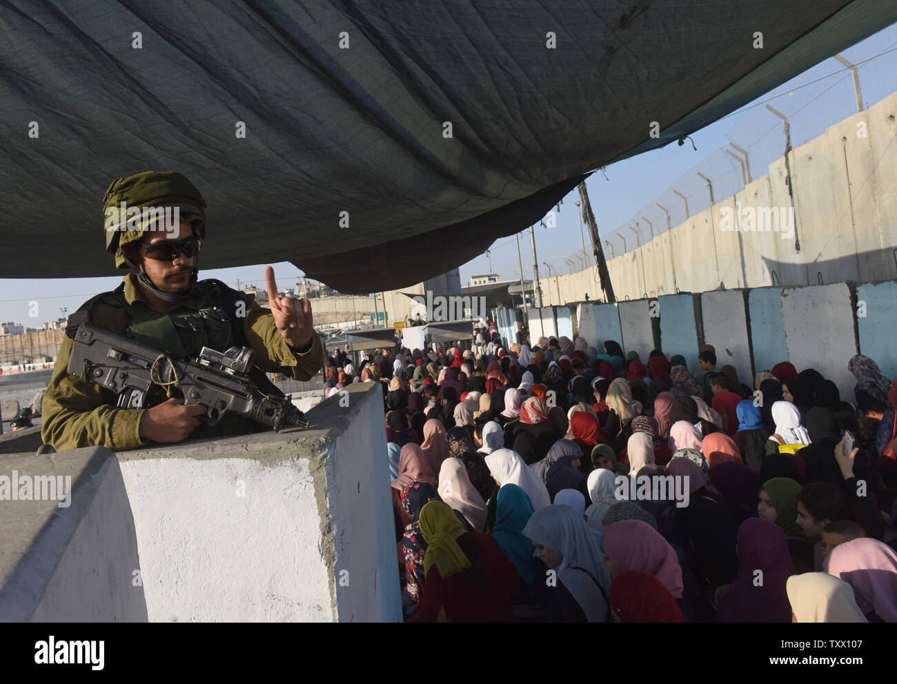 An Israeli soldier motions to Palestinians waiting to cross the Qalandiya checkpoint, West Bank, from Ramallah to Jerusalem, to pray at the Al-Aqsa Mosque on the last Friday of the Muslim holy month of Ramadan, June 8, 2018.  Photo by Debbie Hill/UPI - Stock Image