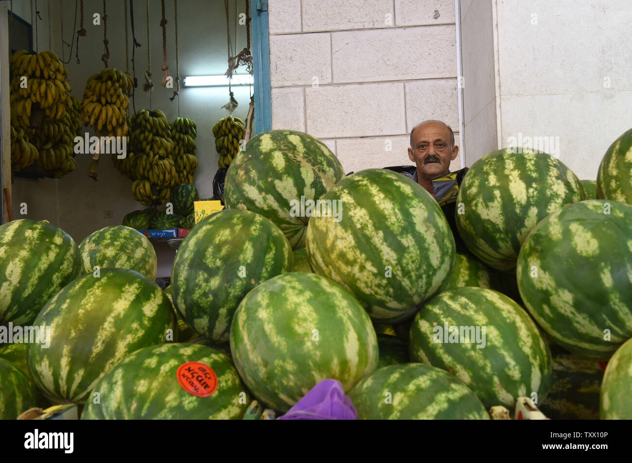 A Palestinian sells watermelons for the Islamic holiday of Eid al-Fitr, in the market in Bethlehem, West Bank, June 13, 2018. Muslims around the world will celebrate the three day holiday of  Eid al-Fitr ,which marks the end of the Muslim holy month of fasting Ramadan.  Photo by Debbie Hill/UPI - Stock Image