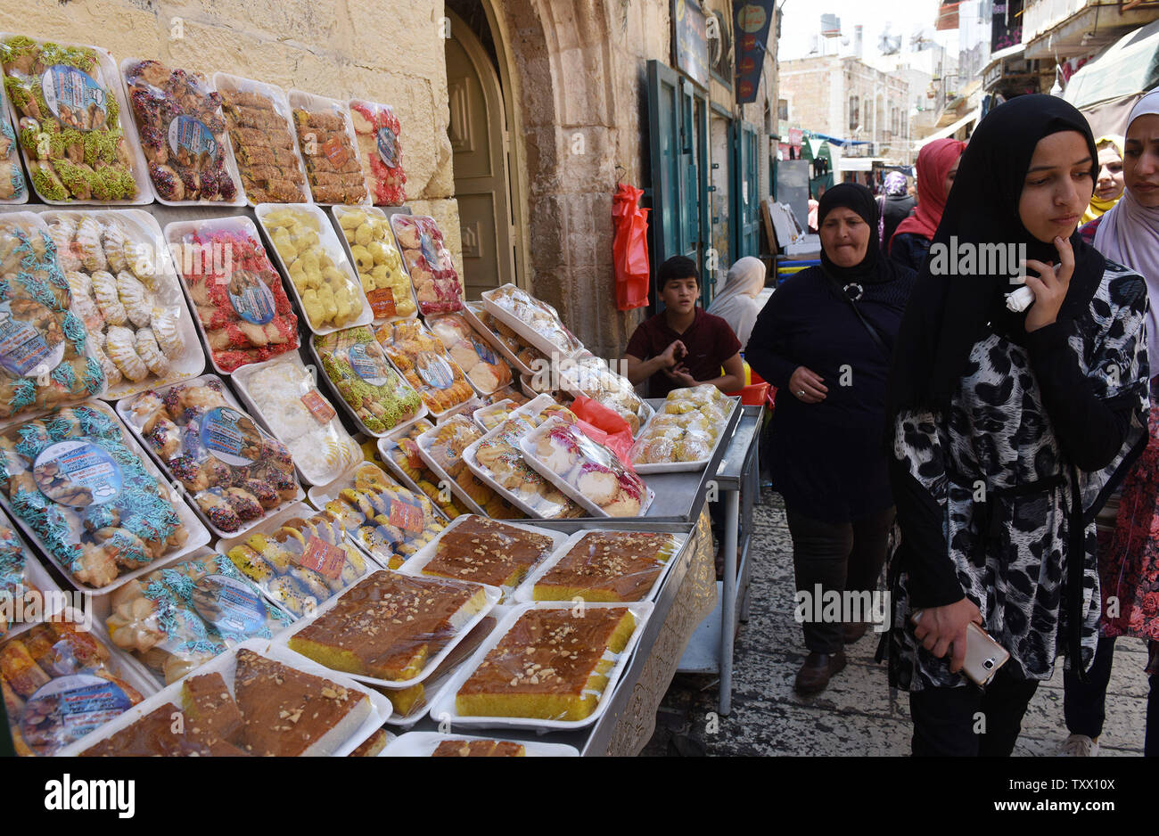 Palestinians walk past special sweets for the Islamic holiday of Eid al-Fitr, in the market in Bethlehem, West Bank, June 13, 2018. Muslims around the world will celebrate the three day holiday of  Eid al-Fitr ,which marks the end of the Muslim holy month of fasting Ramadan.  Photo by Debbie Hill/UPI - Stock Image