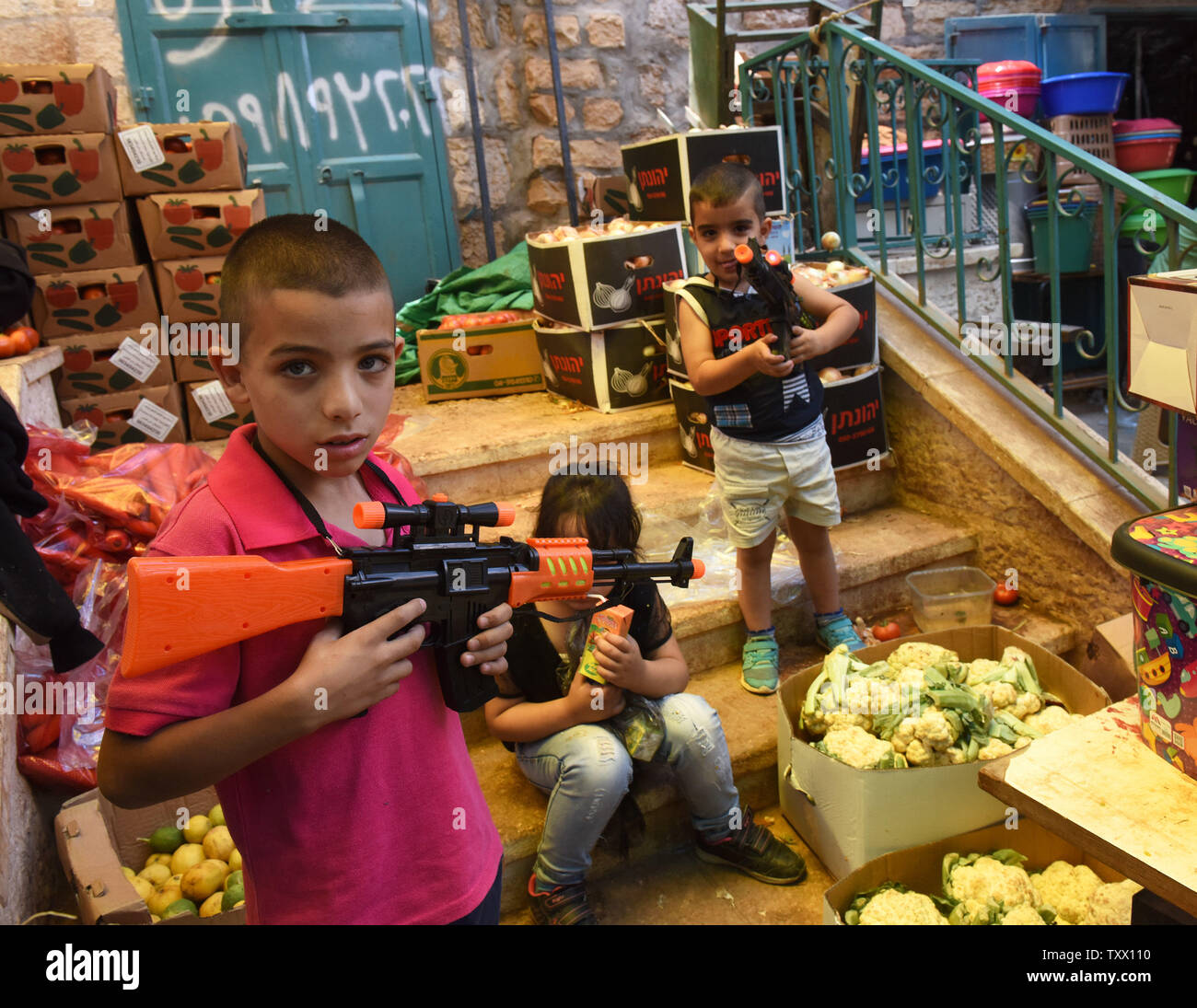 Palestinians play with toy guns before the Islamic holiday of Eid al-Fitr, in the market in Bethlehem, West Bank, June 13, 2018. Muslims around the world will celebrate the three day holiday of  Eid al-Fitr ,which marks the end of the Muslim holy month of fasting Ramadan.  Photo by Debbie Hill/UPI - Stock Image