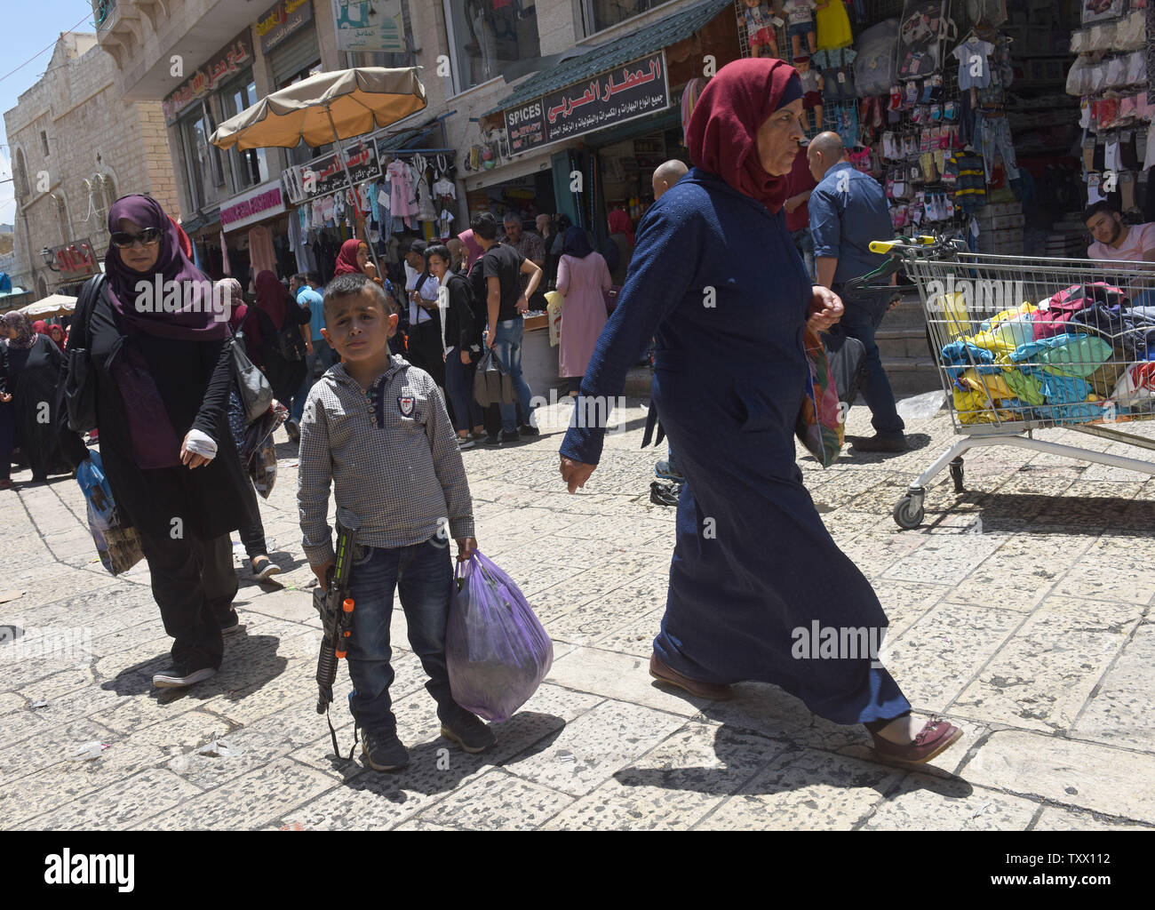 A Palestinian boy holds a toy gun before the Islamic holiday of Eid al-Fitr, in the market in Bethlehem, West Bank, June 13, 2018. Muslims around the world will celebrate the three day holiday of  Eid al-Fitr ,which marks the end of the Muslim holy month of fasting Ramadan.  Photo by Debbie Hill/UPI - Stock Image