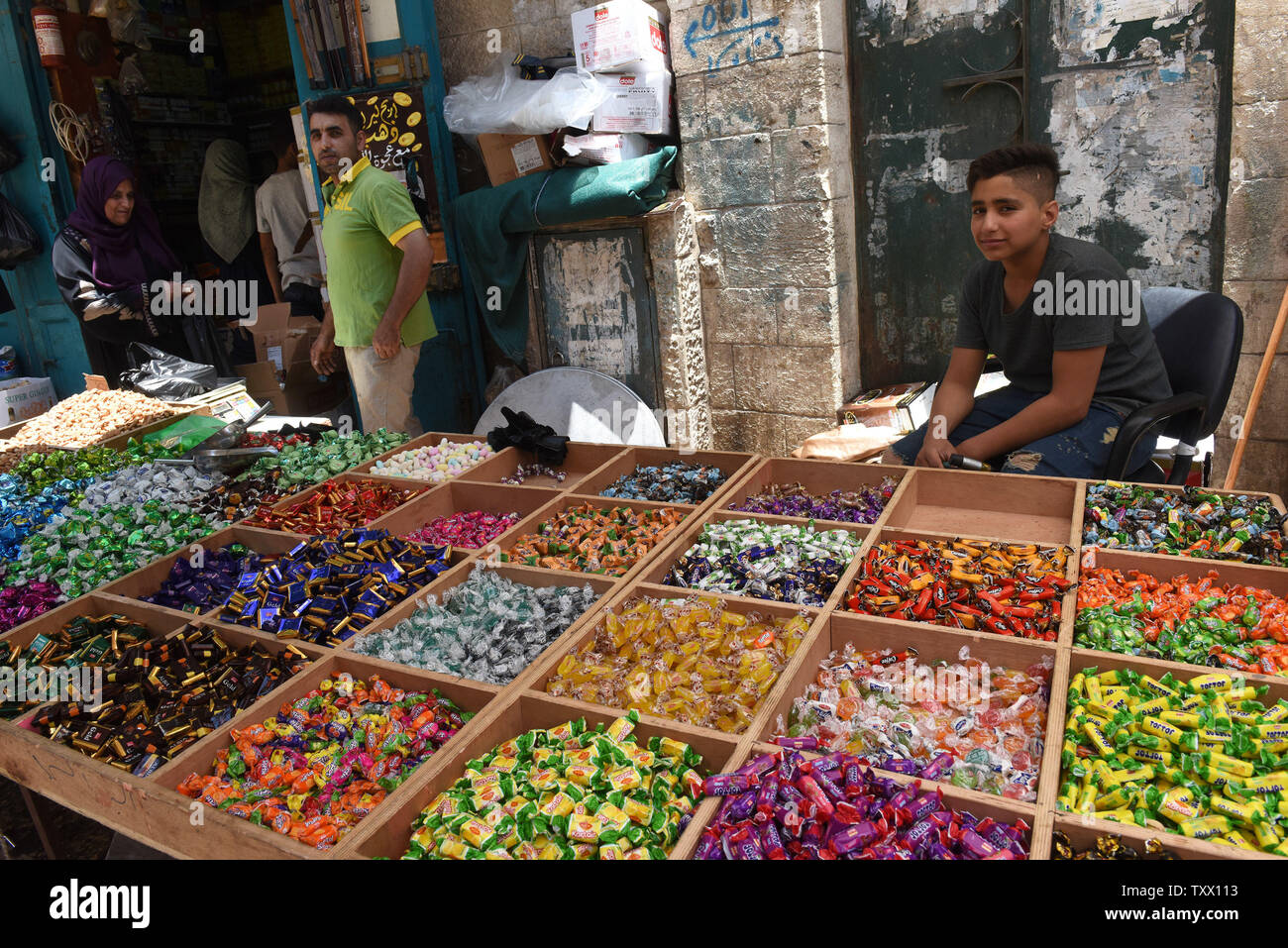 A Palestinian youth sells sweets for the Islamic holiday of Eid al-Fitr, in the market in Bethlehem, West Bank, June 13, 2018. Muslims around the world will celebrate the three day holiday of  Eid al-Fitr ,which marks the end of the Muslim holy month of fasting Ramadan.  Photo by Debbie Hill/UPI - Stock Image