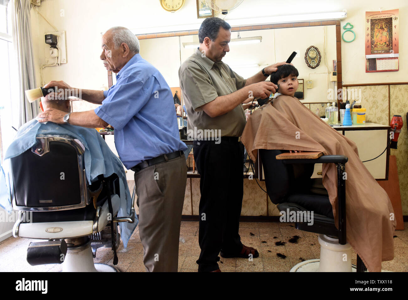 Palestinians get a hair cut before the Islamic holiday of Eid al-Fitr, in the market in Bethlehem, West Bank, June 13, 2018. Muslims around the world will celebrate the three day holiday of  Eid al-Fitr ,which marks the end of the Muslim holy month of fasting Ramadan.  Photo by Debbie Hill/UPI - Stock Image