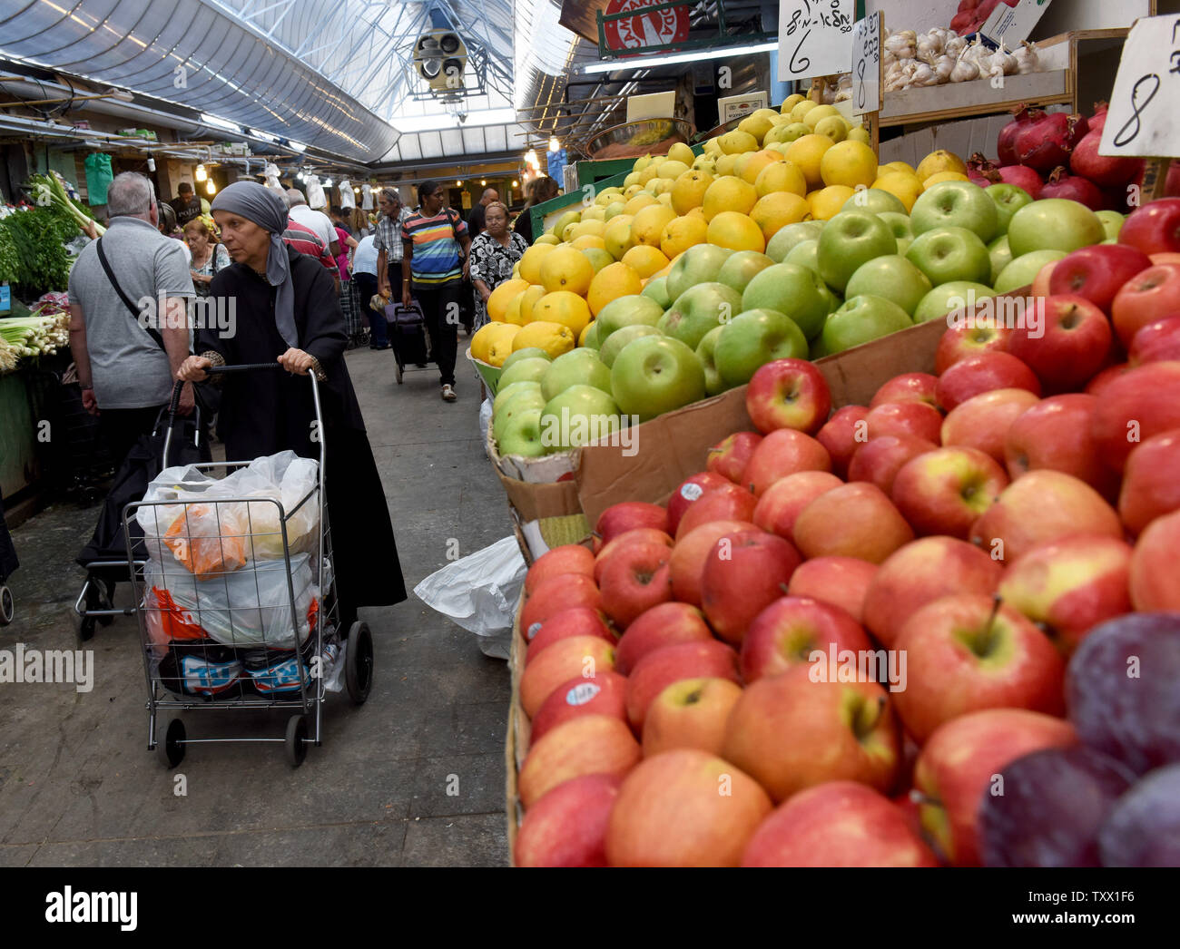An Orthodox Jewish woman shops in the Mahane Yehuda Market in Jerusalem, Israel,  September 5, 2018, in preparation for Rosh HaShana, the Jewish New Year, which starts at sundown on Sunday, September 9, 2018. Pomegranates, apples and honey are traditionally eaten during the Jewish High holidays which is the period of repentance in the Jewish calendar. The abundance of seeds in the pomegranate is associated with the 613 commandments in the Torah and serve as symbols of righteousness and fruitfulness.  Photo by Debbie Hill/UPI - Stock Image