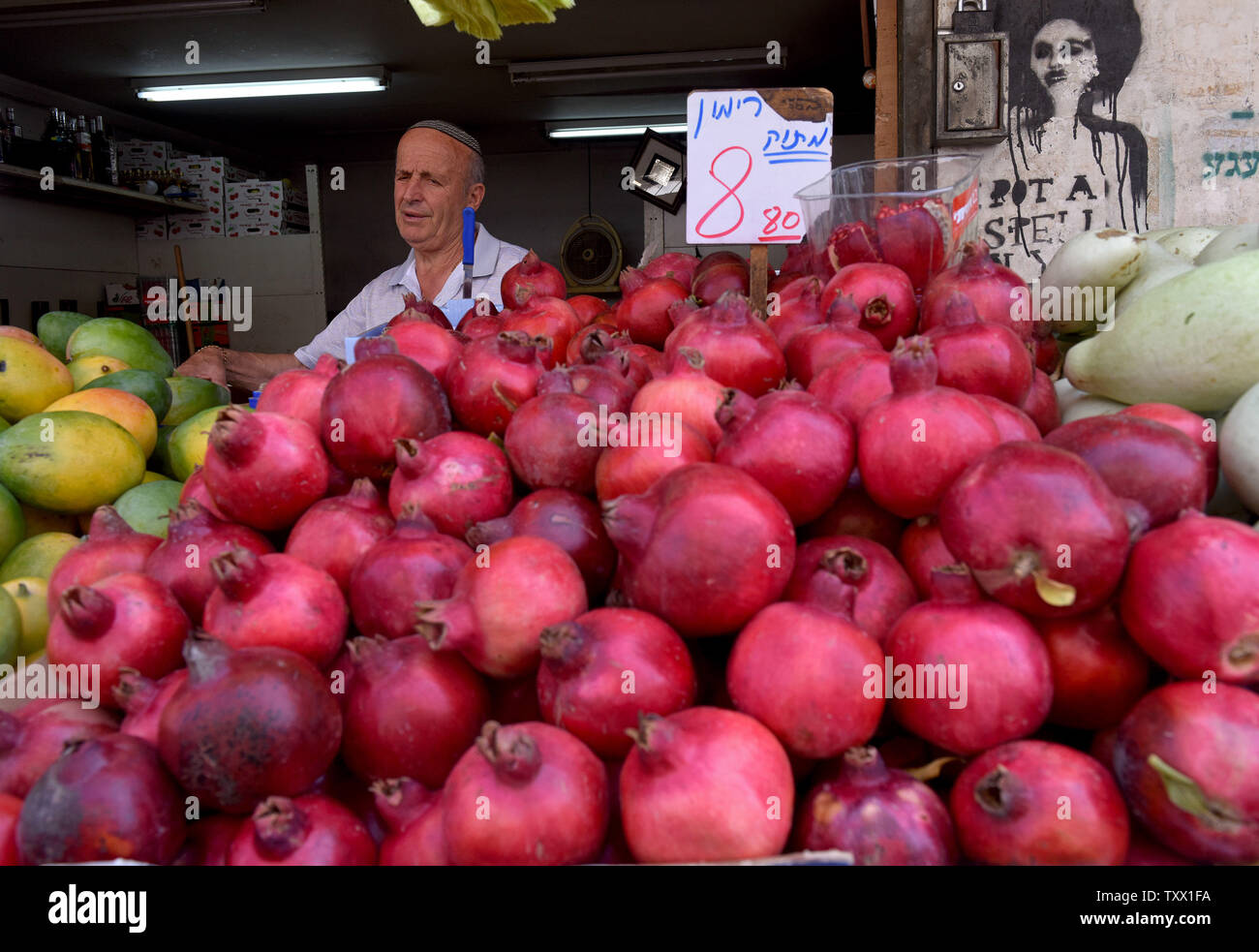 An Israeli sells pomegranates in the Mahane Yehuda Market in Jerusalem, Israel,  September 5, 2018, for Rosh HaShana, the Jewish New Year, which starts at sundown on Sunday, September 9, 2018. Pomegranates, apples and honey are traditionally eaten during the Jewish High holidays which is the period of repentance in the Jewish calendar. The abundance of seeds in the pomegranate is associated with the 613 commandments in the Torah and serve as symbols of righteousness and fruitfulness.  Photo by Debbie Hill/UPI - Stock Image