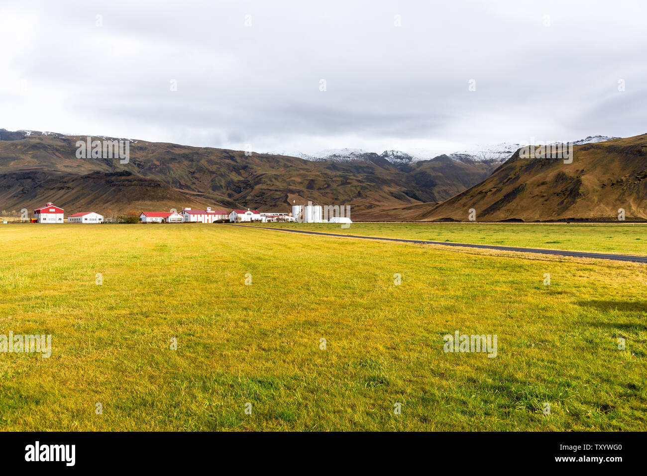 Meadow with farm buildings at the far edge and mountains in background in Iceland on a sunny fall day - Stock Image