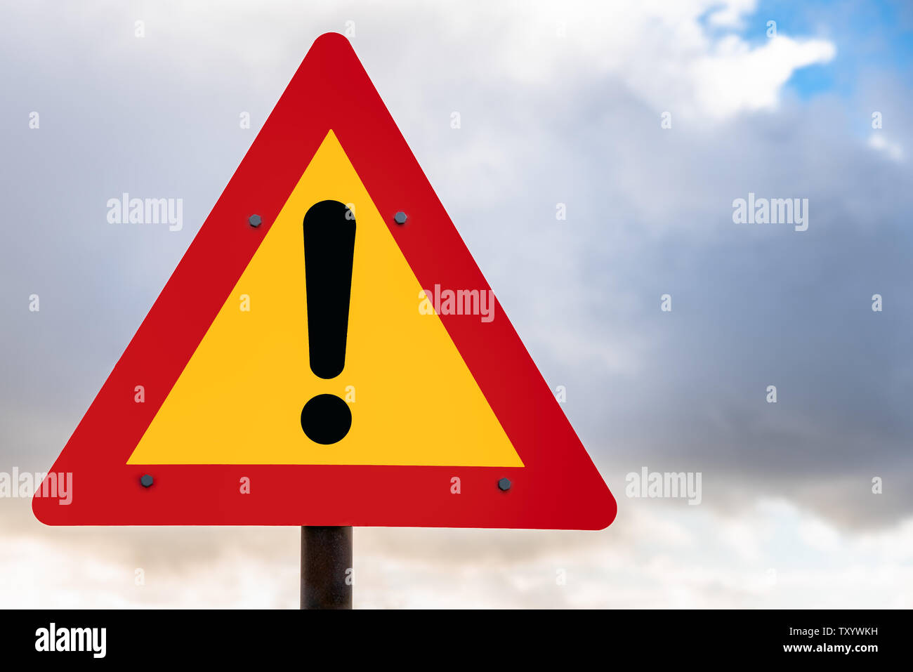 Hazard ahead warning road sign against cloudy sky - Stock Image