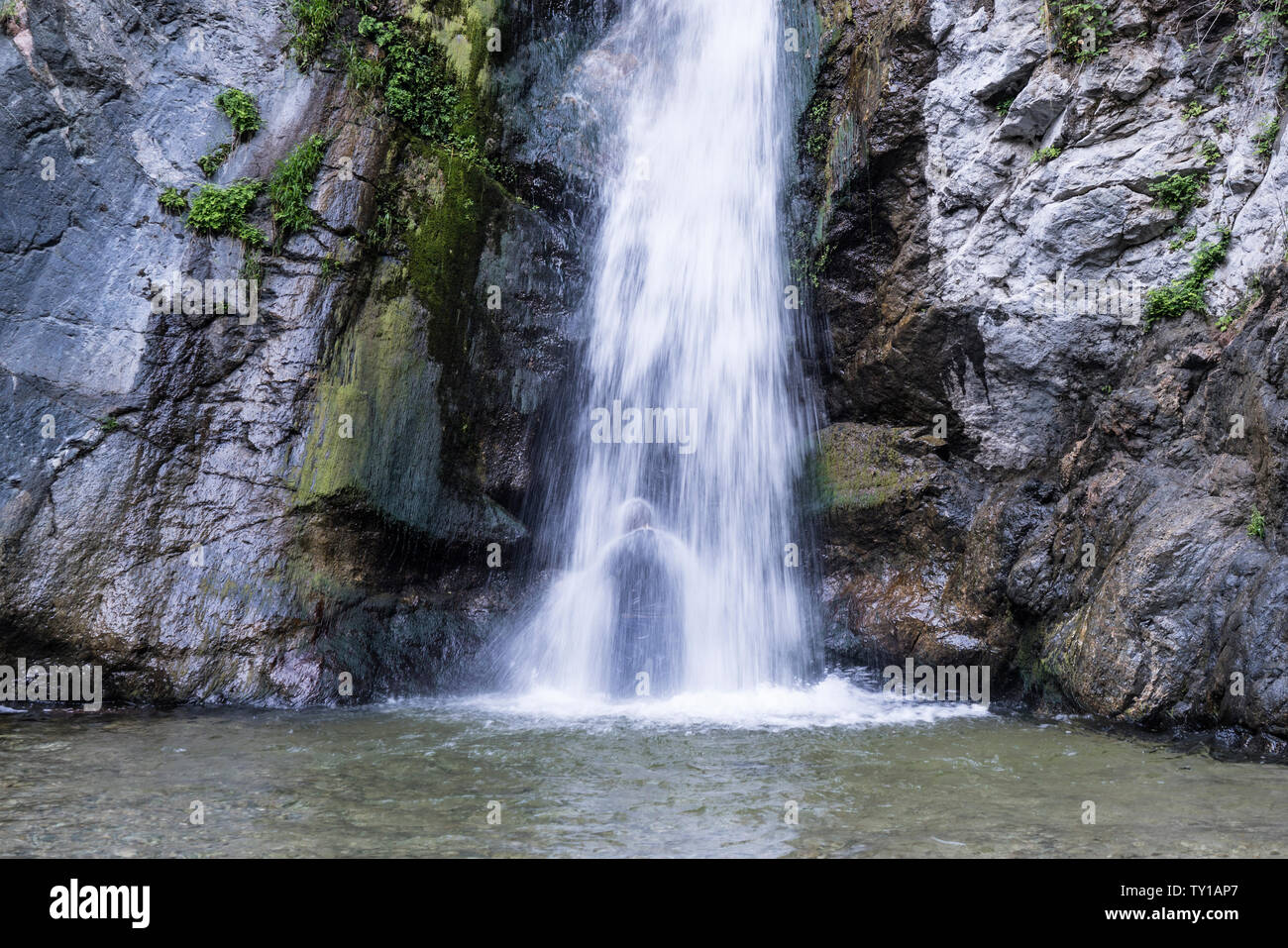 Los Angeles County, California, USA - June 23, 2019:  Silhouette of person cooling off under Eaton Falls in the San Gabriel Mountains near Pasadena in Stock Photo