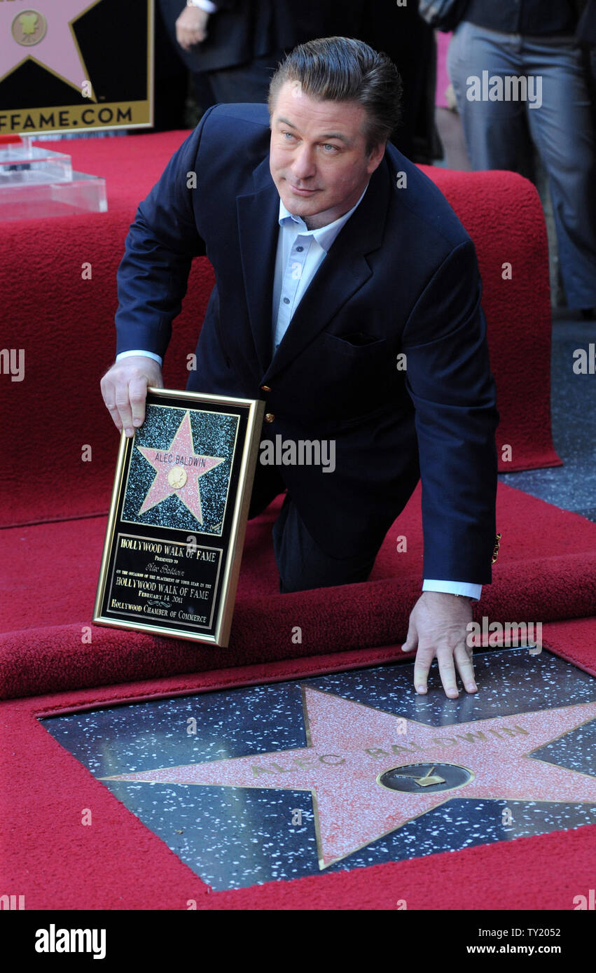 Actor Alec Baldwin holds a replica plaques as he touches his star during an unveiling ceremony honoring him with the 2,433rd star on the Hollywood Walk of Fame in Los Angeles on February 14, 2011.  UPI/Jim Ruymen Stock Photo