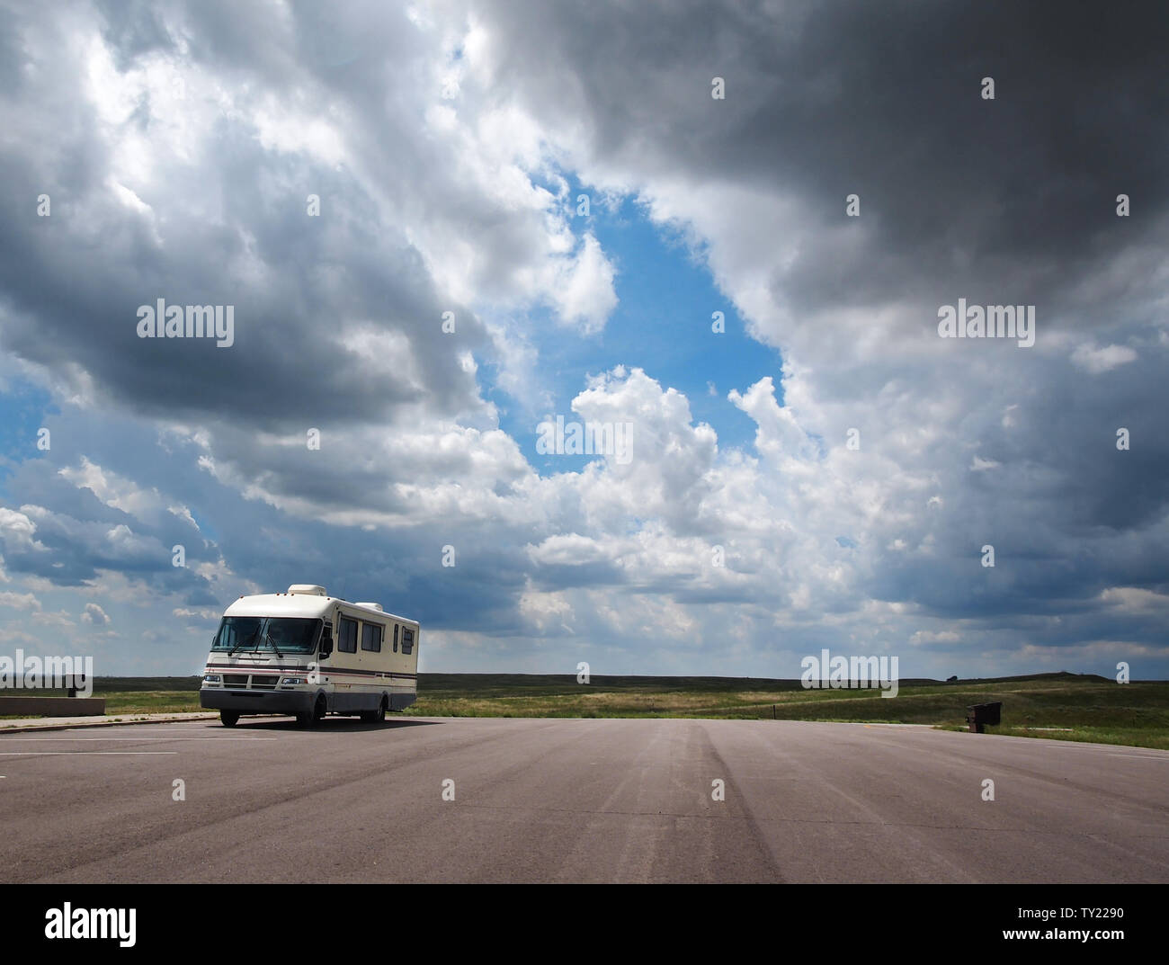 A recreational vehical is parked at a highway rest stop and scenic overlook out in the Nebraska prairie under a big sky with dramatic clouds. Stock Photo