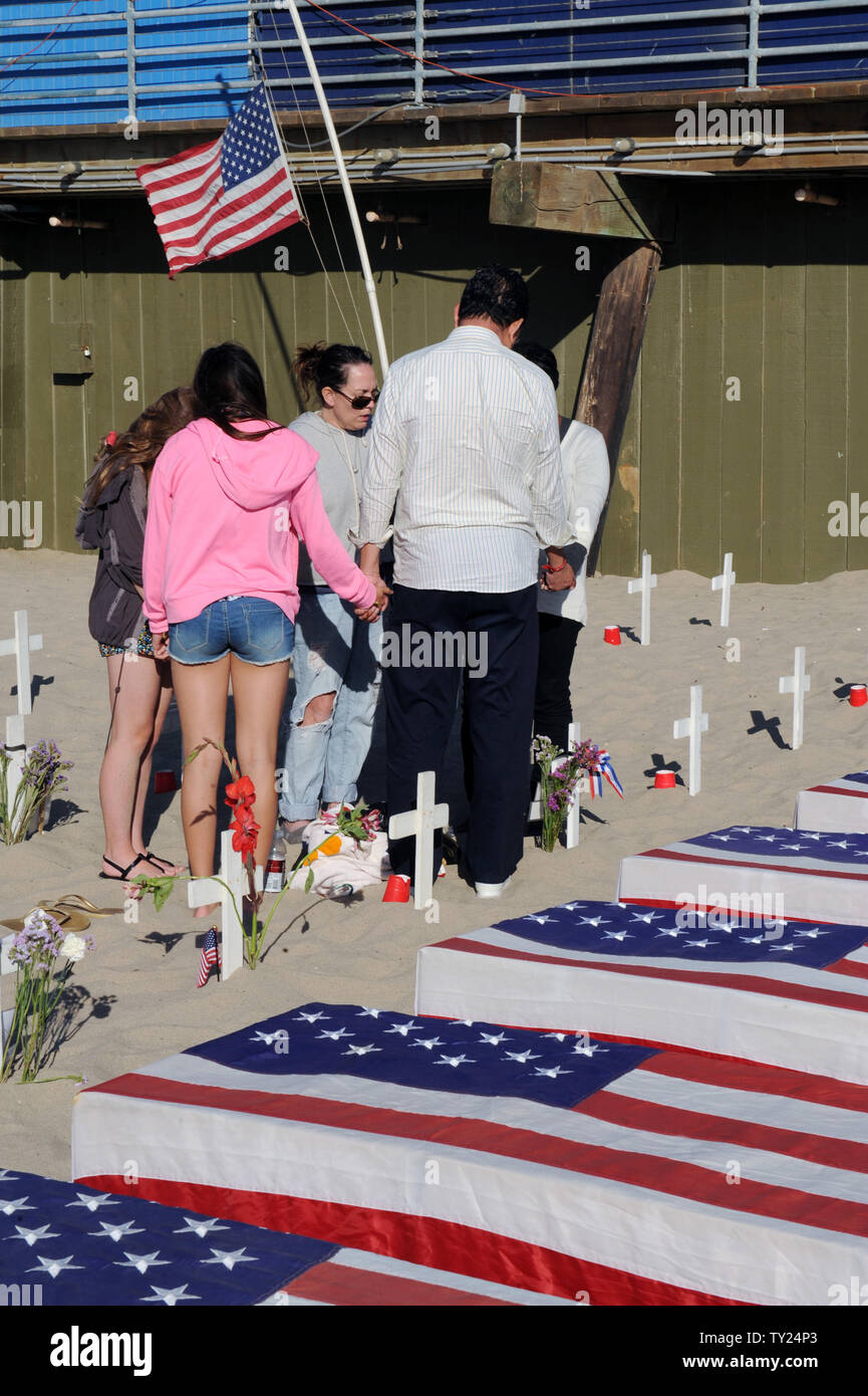 A group of people hold hands in prayer at the Arlington West Memorial Project in Santa Monica, California on May 29, 2011. The 12 mock caskets they are next to represent the soldiers killed this week: 10 in Afghanistan and 2 in Iraq.    UPI /Jim Ruymen) - Stock Image