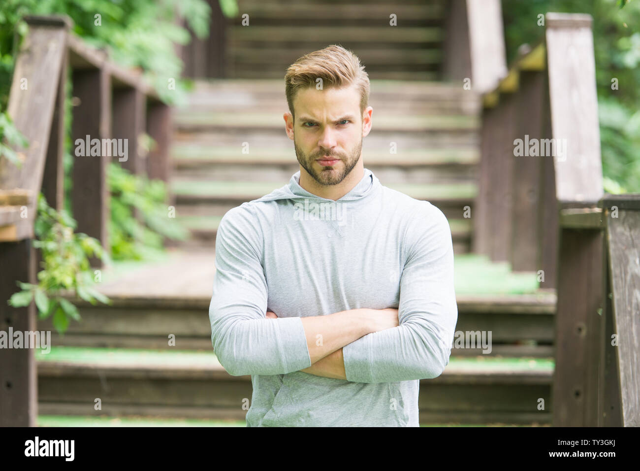 Overcome any obstacles. Sportsman lifestyle. Handsome athlete stairs background. Male beauty. Sport wellbeing and self care. Handsome man sporty outfit look confident. Guy handsome bearded face. - Stock Image