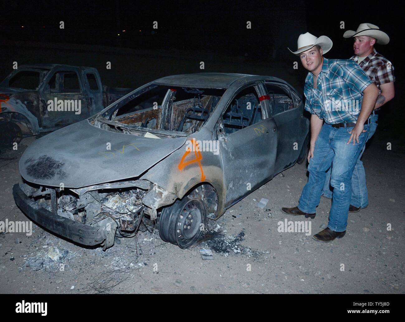 Two men examine one of 30 cars destroyed when a brush fire