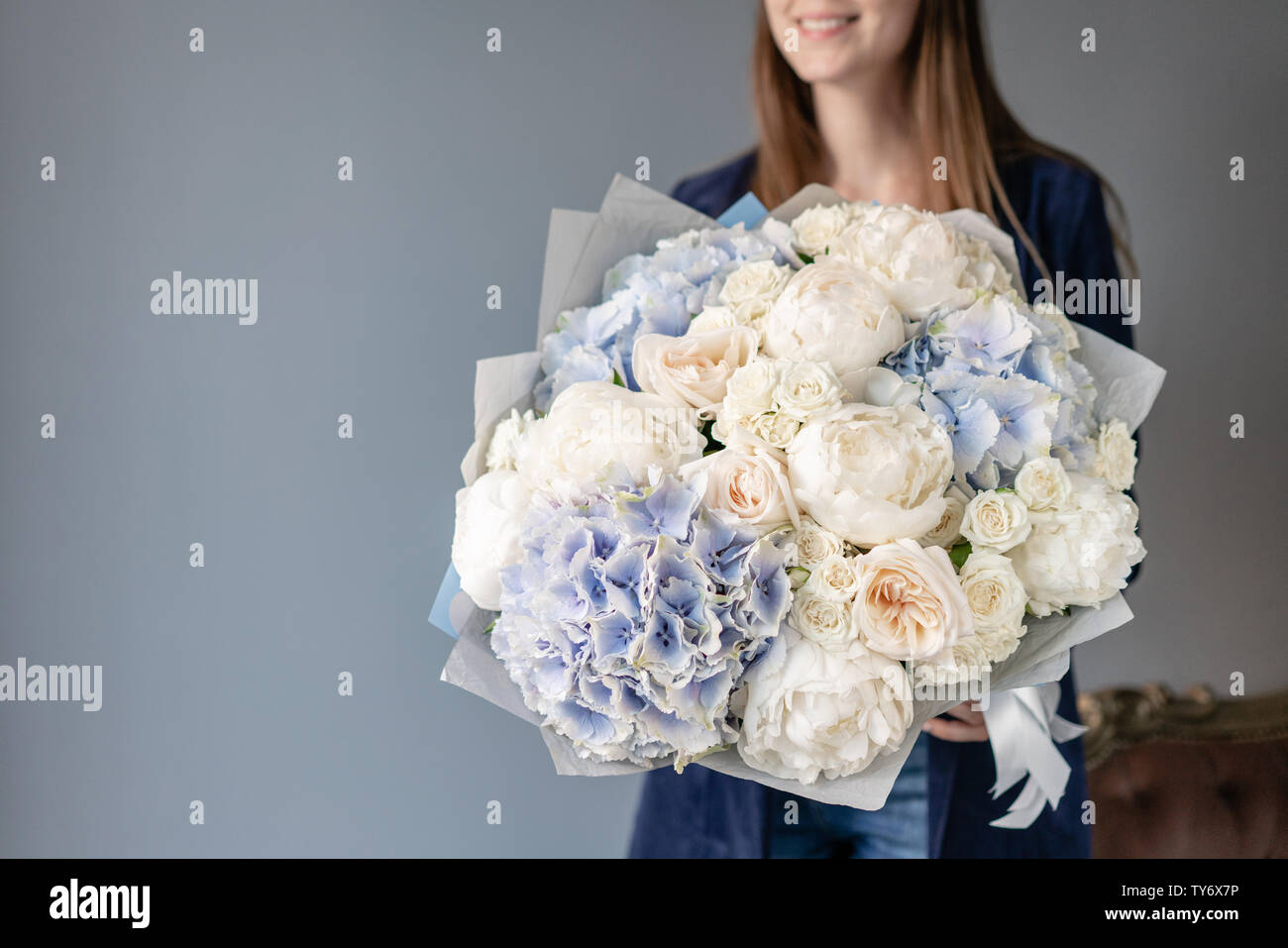 White peonies and blue hydrangea. Beautiful bouquet of mixed flowers in woman hand. Floral shop concept . Handsome fresh bouquet. Flowers delivery Stock Photo