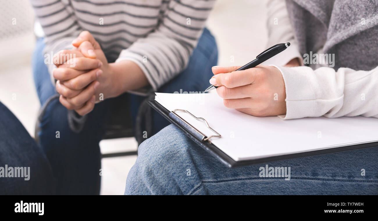 Psychiatrist taking notes during group therapy of support group Stock Photo