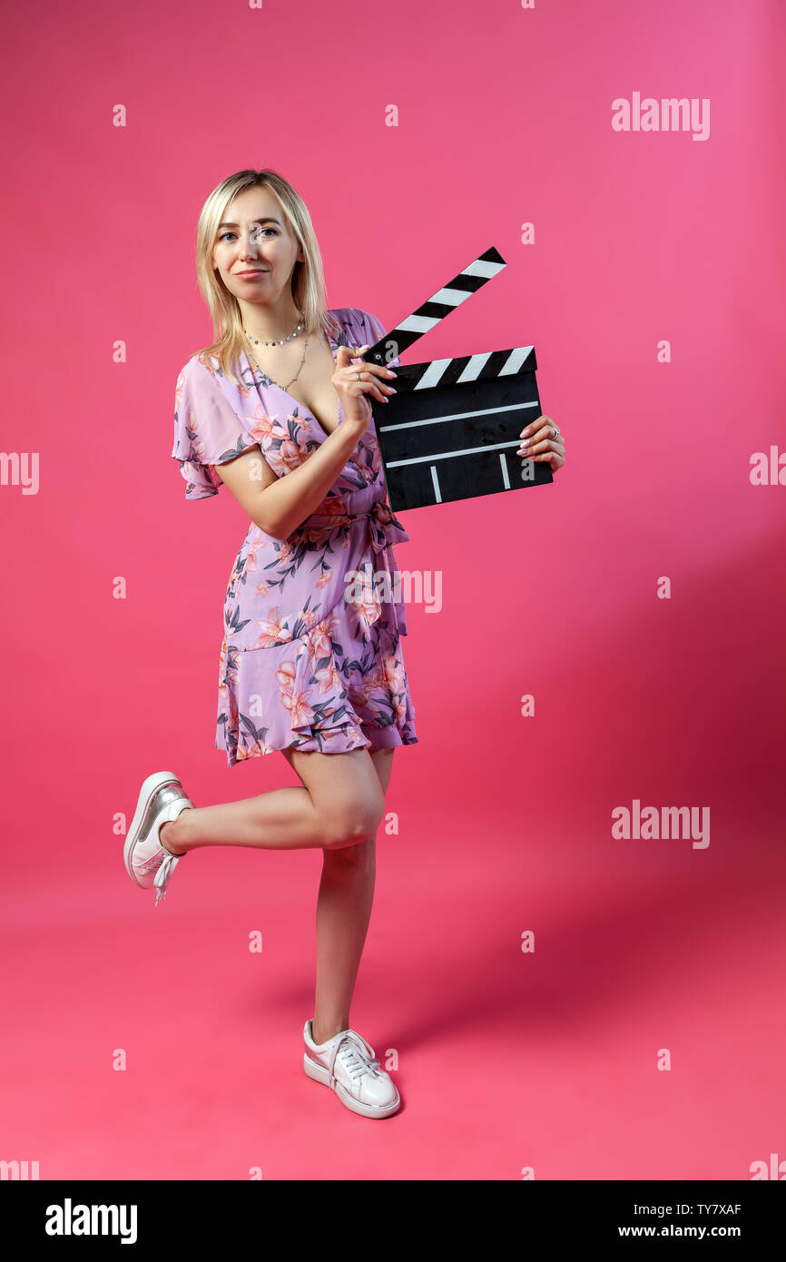 Beautiful blonde woman in a purple sundress holds an open clapperboard filmmaker in black with white stripes to start shooting a film and lifts one le Stock Photo