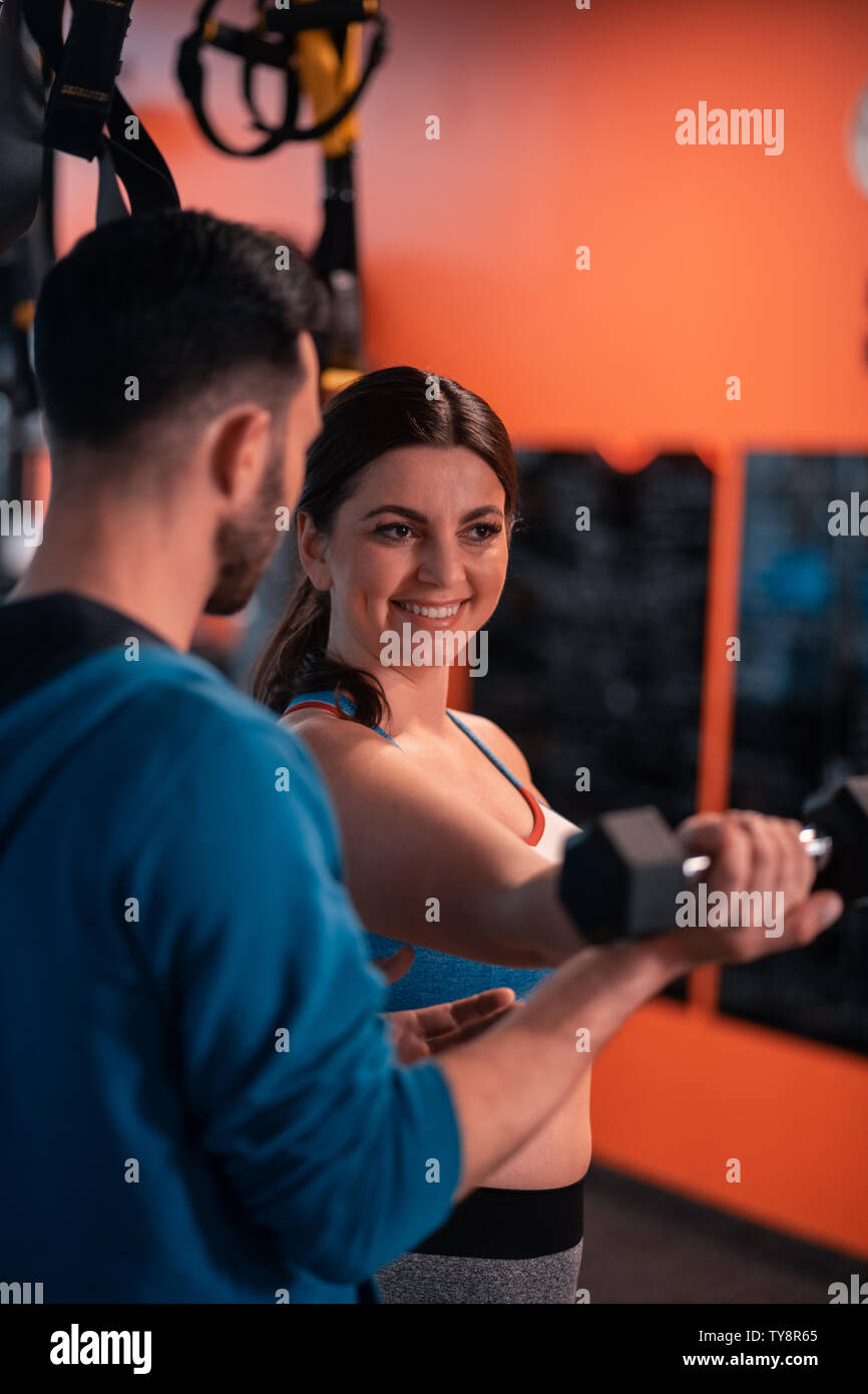 Woman smiling while talking to trainer and doing exercises Stock Photo