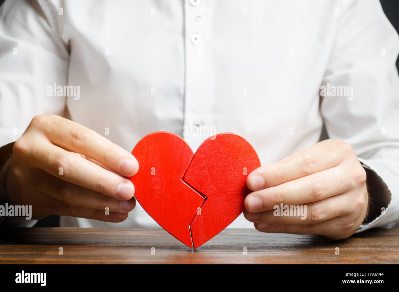 A man collects a broken heart in his hands. Concept of love and relationships. Family psychotherapist services. Reconciliation. Saving the family. Sea Stock Photo