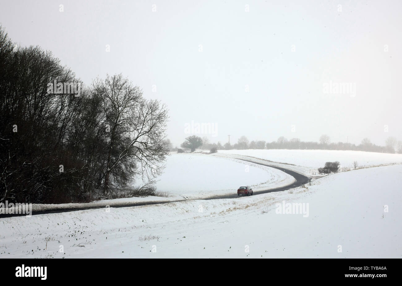 A car drives through a snow covered field in South-East England as temperatures fall below zero in the United Kingdom and across Europe on February 06 2012.         UPI/Hugo Philpott - Stock Image