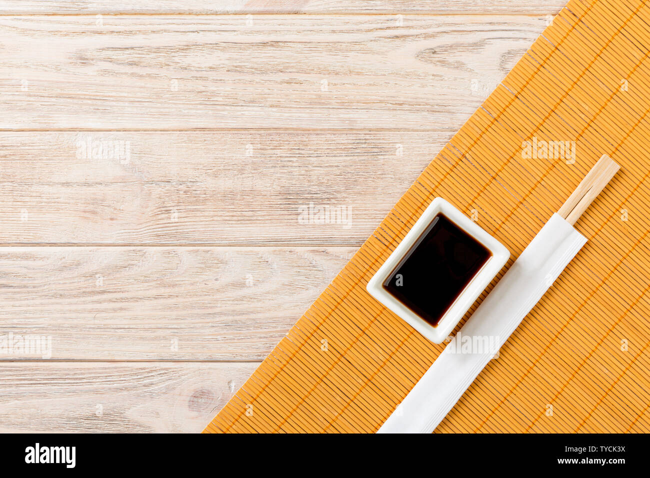 Bamboo Mat And Soy Sauce With Sushi Chopsticks On Wooden