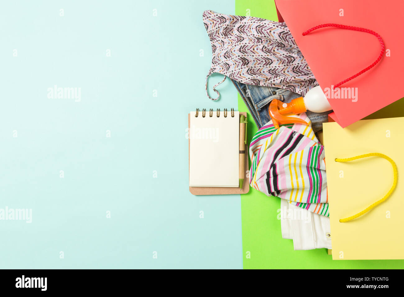 Summer concept of colourful shopping bags full of clothes. Gift bags with T-shirt, denim shorts, notebook and bottle of sunscreen. Summer wishlist con - Stock Image