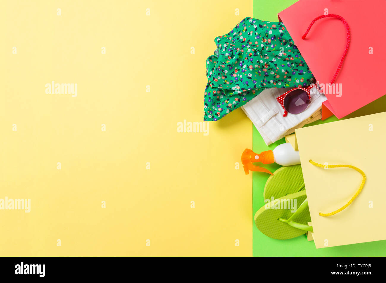 Summer concept of colourful shopping bags full of clothes. Gift bags with T-shirt, denim shorts, flip flops and bottle of sunscreen. Summer wishlist c - Stock Image