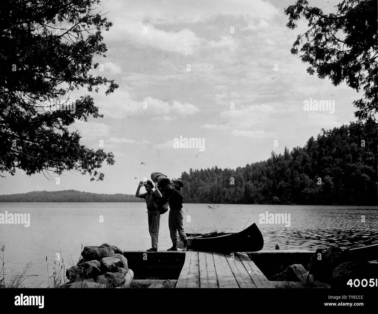 Photograph of Two Vacationists; Scope and content:  Original caption: Two vacationists getting ready to pack their duffel and canoe over the portage out of West Bearskin Lake into Duncan Lake. Stock Photo
