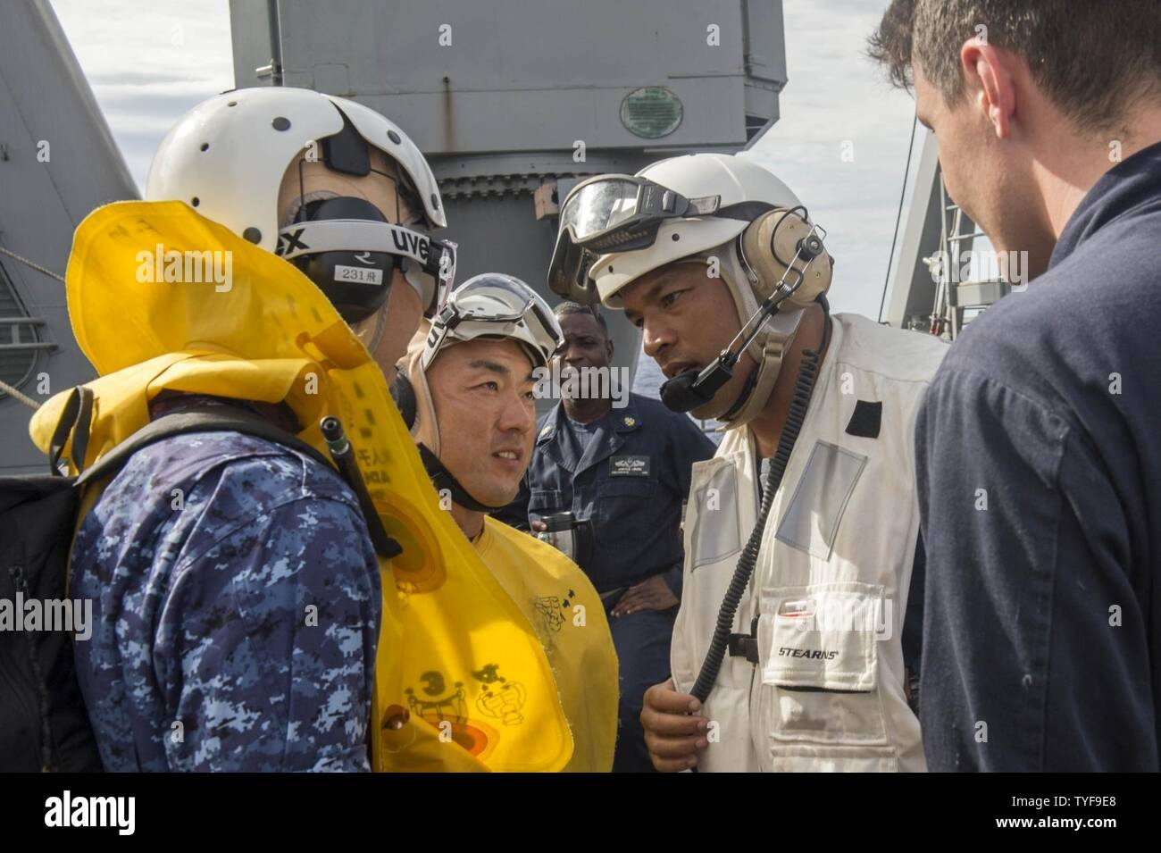 PACIFIC OCEAN (Nov. 6, 2016) Cmdr. Gervy Alota, commanding officer of amphibious dock landing ship USS Comstock (LSD 45) greets Lt. j.g. Shogo Kudo, left, and Petty Officer 2nd Class Kazuhiko Iwanatsu, center, as they embark Comstock for Keen Sword 17. Keen Sword 17 is a joint and bilateral field training exercise (FTX) between U.S. and Japanese forces meant to increase readiness and interoperability within the framework of the U.S.-Japan alliance. - Stock Image